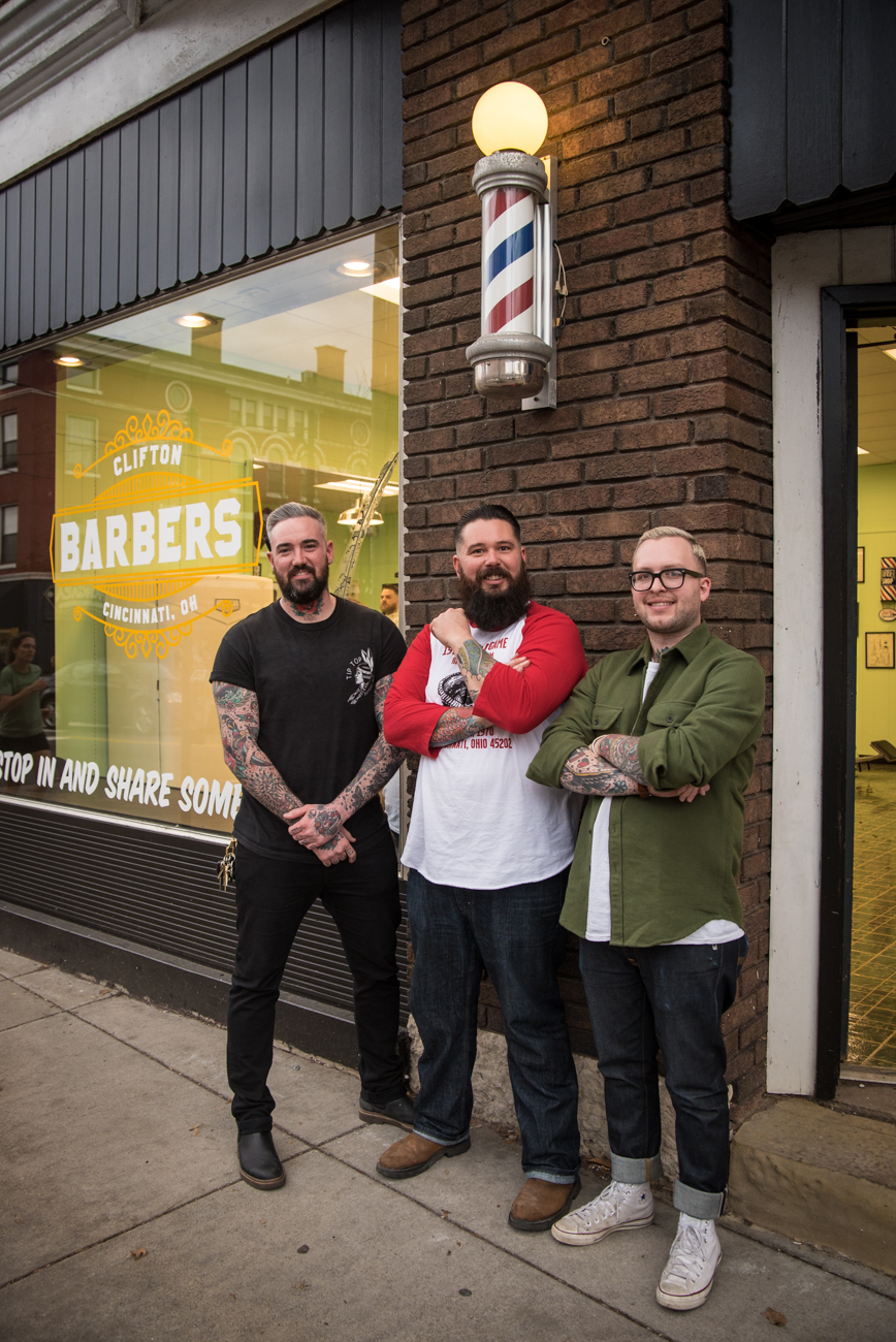 Brandon Cornell, owner Andy Mobarry, and Blake Siebenburgen are pictured outside Clifton Barbers at 337 Ludlow Avenue. They are working towards finishing school and will become full-time barbers at the shop. / Image: Melissa Doss Sliney // Published: 3.13.17
