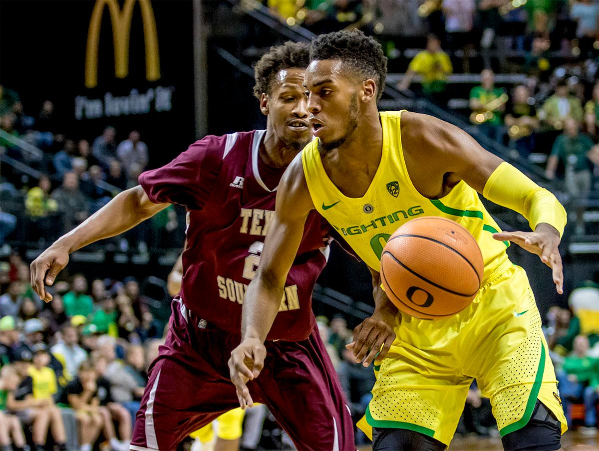 The Duck's Troy Brown (#0) looks for an opening towards the basket as he dribbles the ball. The Oregon Ducks defeated Texas Southern Tigers 74-68. The Ducks are now 7-3 overall in the Pac-12. Photo by August Frank. Oregon News Lab