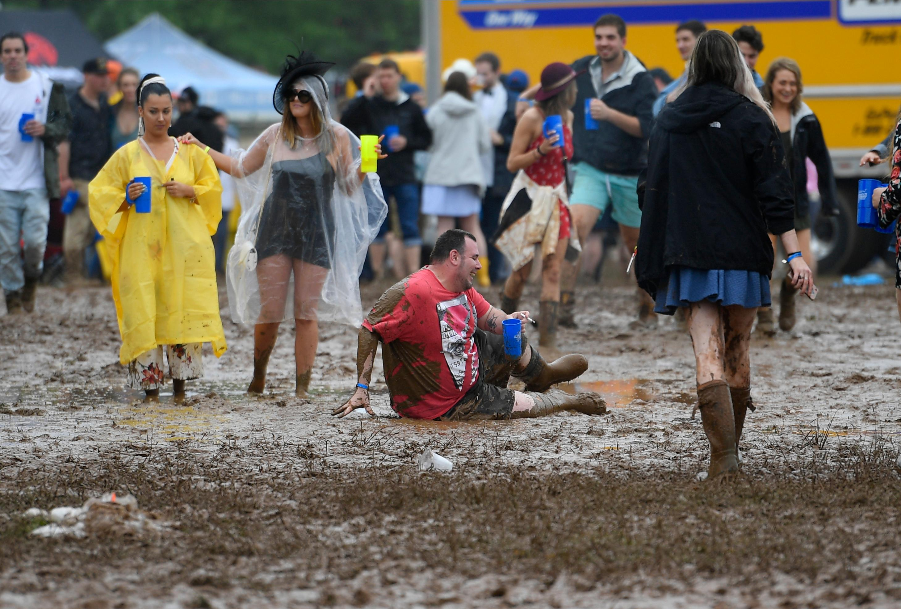 A man falls on a muddy infield during the 143rd Preakness Stakes horse race at Pimlico race course, Saturday, May 19, 2018, in Baltimore. (AP Photo/Nick Wass)