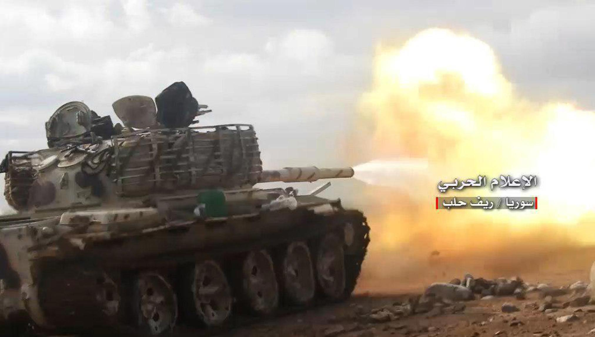 This photo provided on Saturday, Jan. 20, 2018, by the government-controlled Syrian Central Military Media, shows a Syrian government forces tank firing during a battle against the Syrian opposition fighters, in the southern Aleppo countryside, Syria. Syrian state TV says government forces have retaken a key air base in northwest Syria that was lost to rebels in 2015. The state broadcaster says Syrian troops fought their way into the strategic Abu Zuhour air base on Saturday, in Idlib province. (Syrian Central Military Media, via AP)