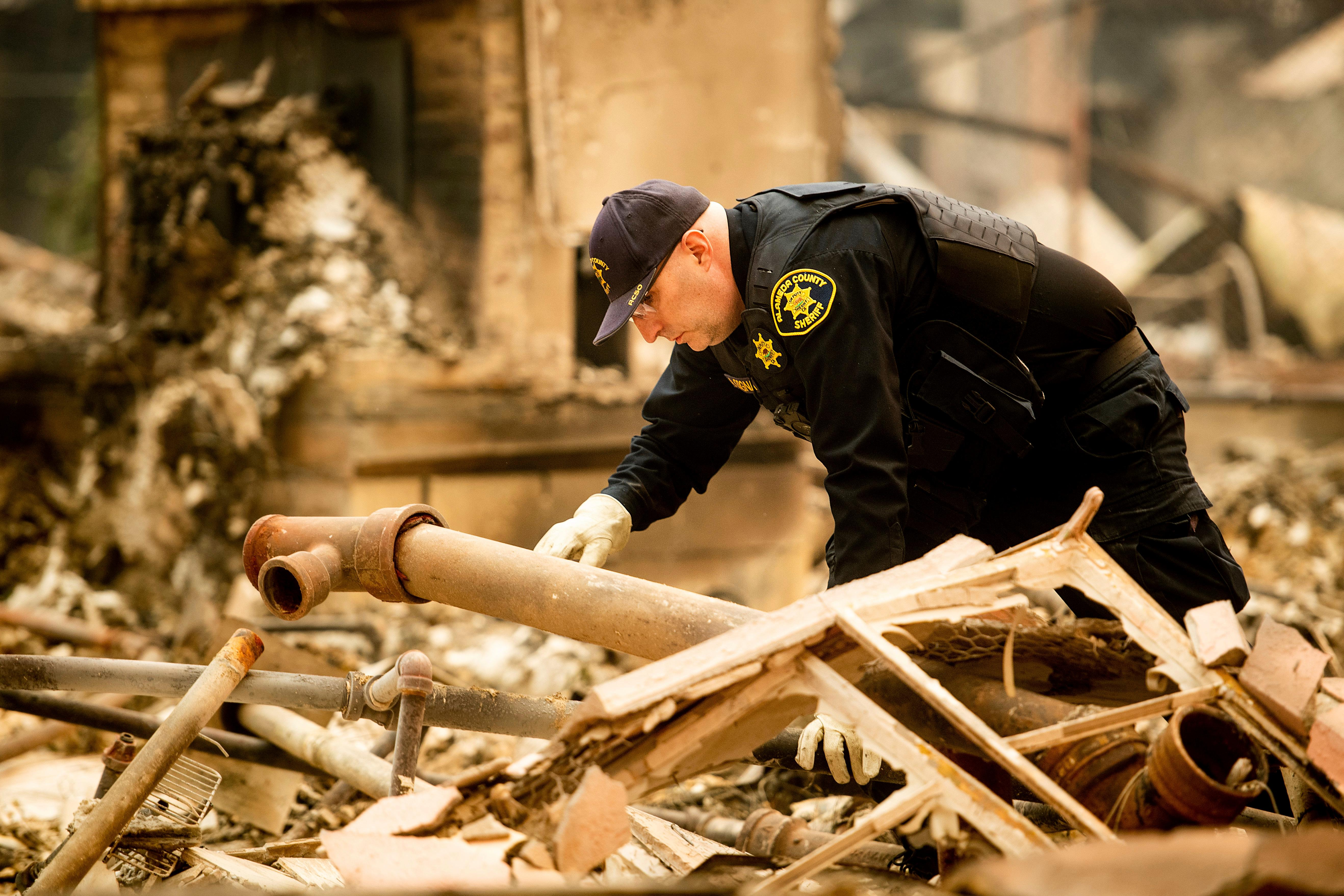 Alameda County Sheriff's deputy A. Gogna searches for victims of the Camp Fire on Monday, Nov. 12, 2018. (AP Photo/Noah Berger)