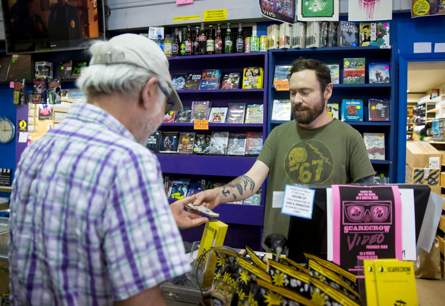 <p>Day Manager Jason Dodson helps a customer at Scarecrow Video, the film rental store that has been serving Seattle for 30 years. In 2014, the collection had grown to become such a significant archive that a non-profit was formed. The store continues to grow at a rate of 3,000-5,000 titles each year, representing 129 countries and over 126 languages. (Sy Bean / Seattle Refined)</p>