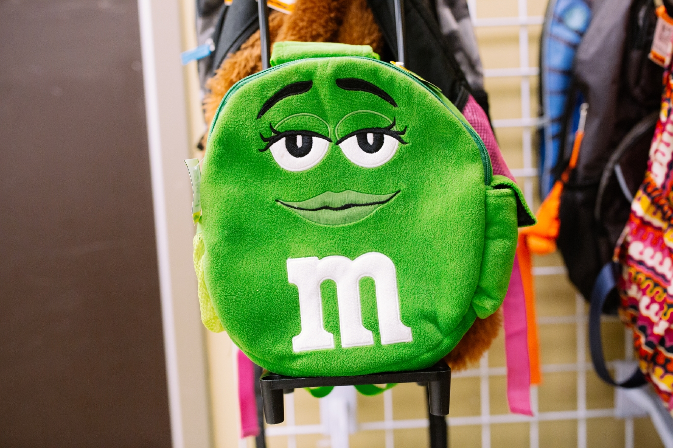 Green M&M rolling backpack. $4.99  Are you going to a White Elephant Gift Exchange this year? We headed to our local Value Village to give you some gift ideas and how much they cost. (Image: Joshua Lewis / Seattle Refined)
