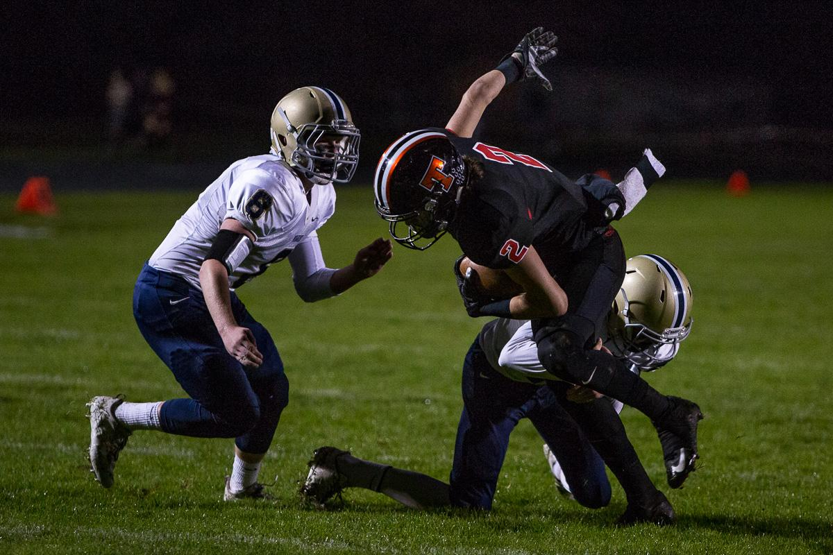 Marist Spartan Jace Krier (#8) and his teammate put pressure on Thurston's D.J. Stedman (#2). The Thurston Colts defeated the Marist Catholic Spartans 50 – 14 to seal second place in their conference at Thurston High School on Friday, October 13. Photo by Kit MacAvoy, Oregon News Lab