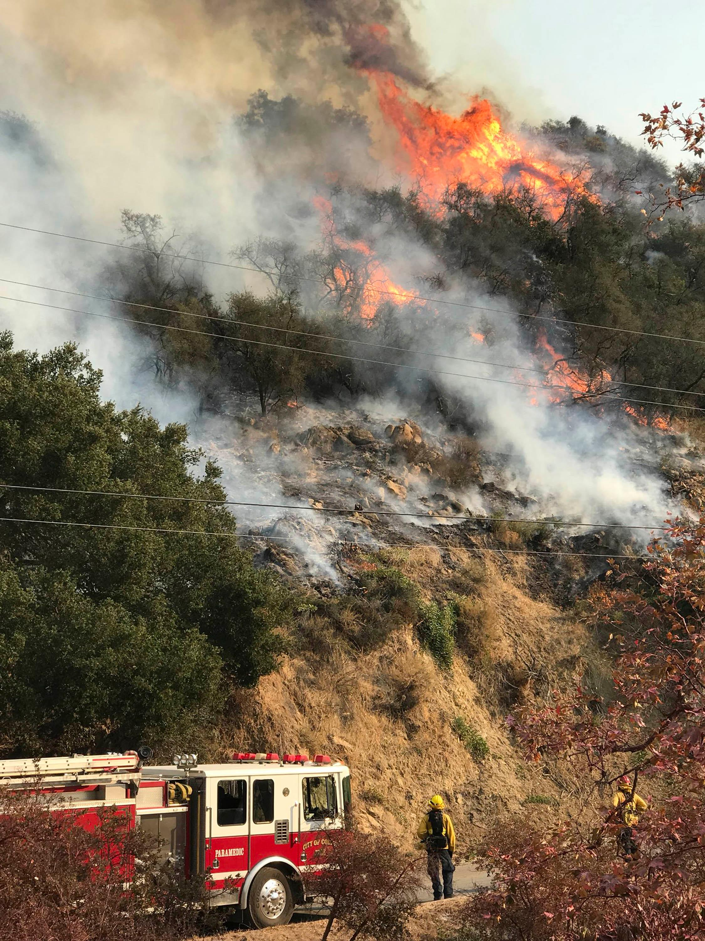 In this photo provided by the Santa Barbara County Fire Department, an engine company from the city of Colton, Calif., operating under mutual aid, keeps watch on pockets of burning and unburned vegetation off Bella Vista Dr. in Montecito, Calif., Wednesday, Dec. 13, 2017. After announcing increased containment on the Thomas fire, one of the biggest wildfires in California history, officials Wednesday warned that communities remain at risk and the threat could increase as unpredictable winds whip up again. (Mike Eliason/Santa Barbara County Fire Department via AP)