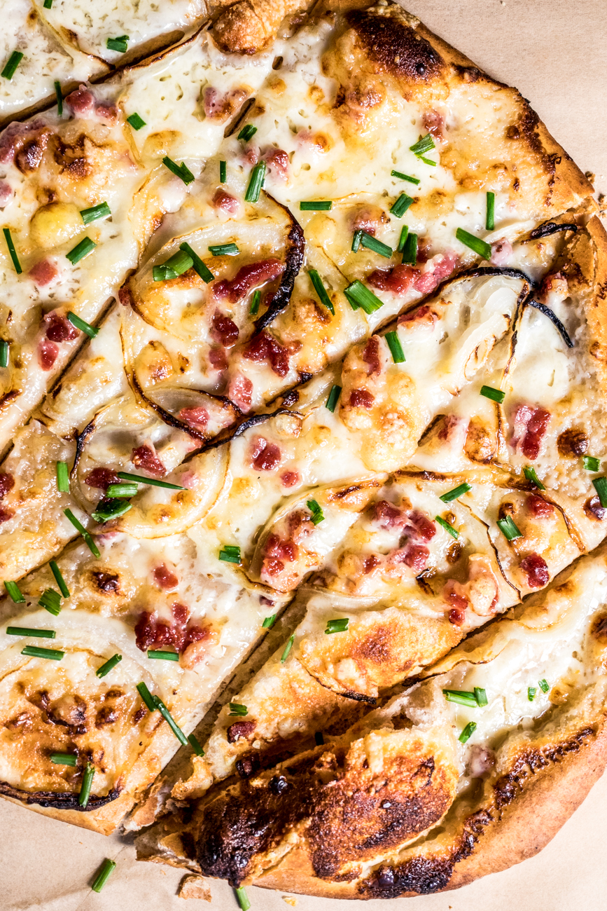 Flammekueche: a southwestern German style pizza on sourdough topped with crème fraîche, thinly sliced onions, Swiss cheese, and black forest ham / Image: Catherine Viox{ }// Published: 12.17.19