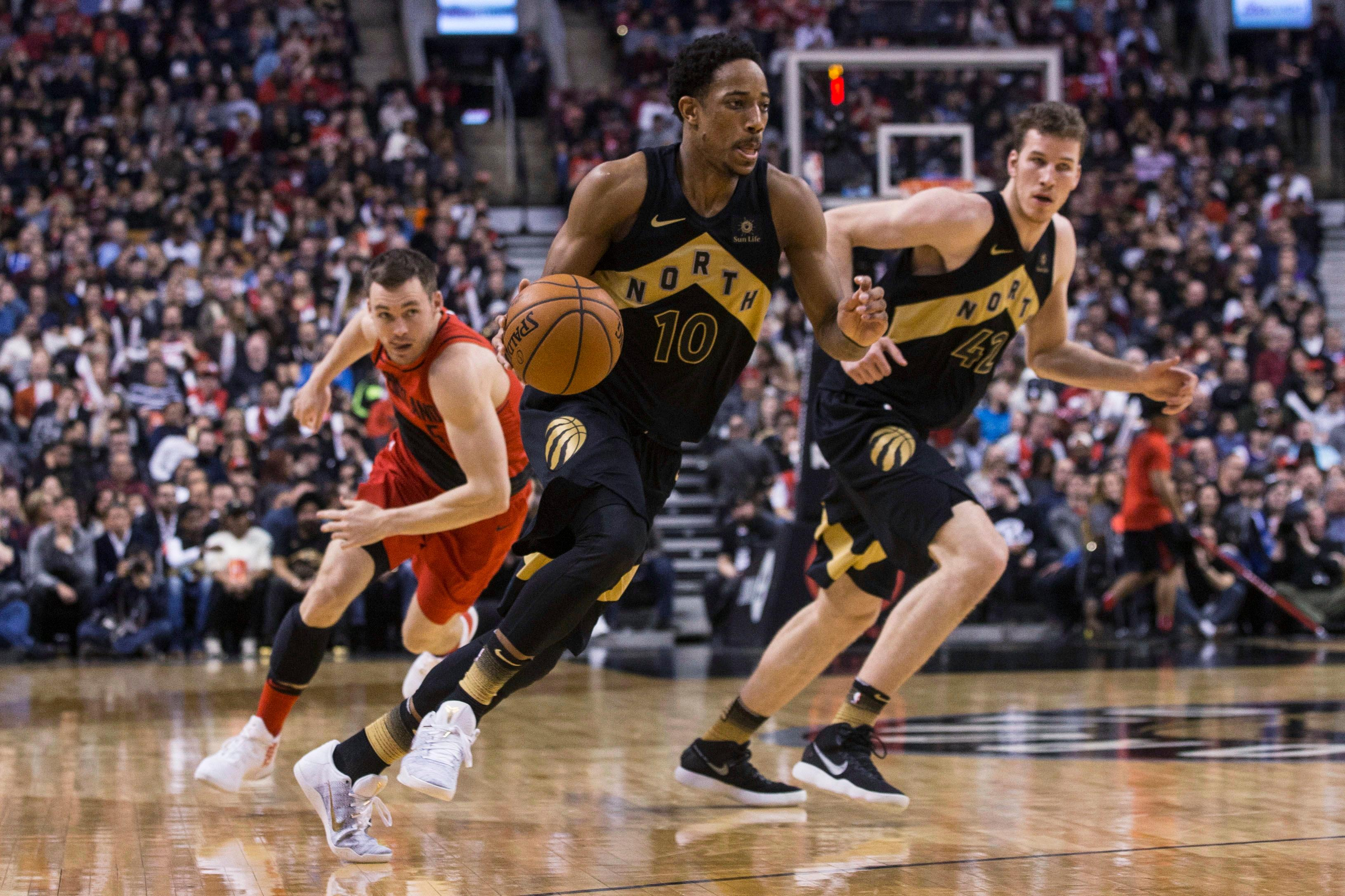 Toronto Raptors' DeMar DeRozan drives past Portland Trail Blazers' Pat Connaughton, left, as Raptors' Jakob Poeltl watches during the second half of an NBA basketball game Friday, Feb. 2, 2018, in Toronto. (Chris Young/The Canadian Press via AP)