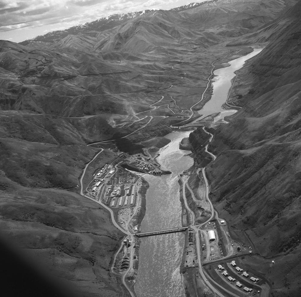 Brownlee Dam site during construction. Near the bottom of the photo is the bridge linking Oregon Highway 86 to Idaho Highway 71.  (Pete Basche/Baker County Historic Photo Collection)