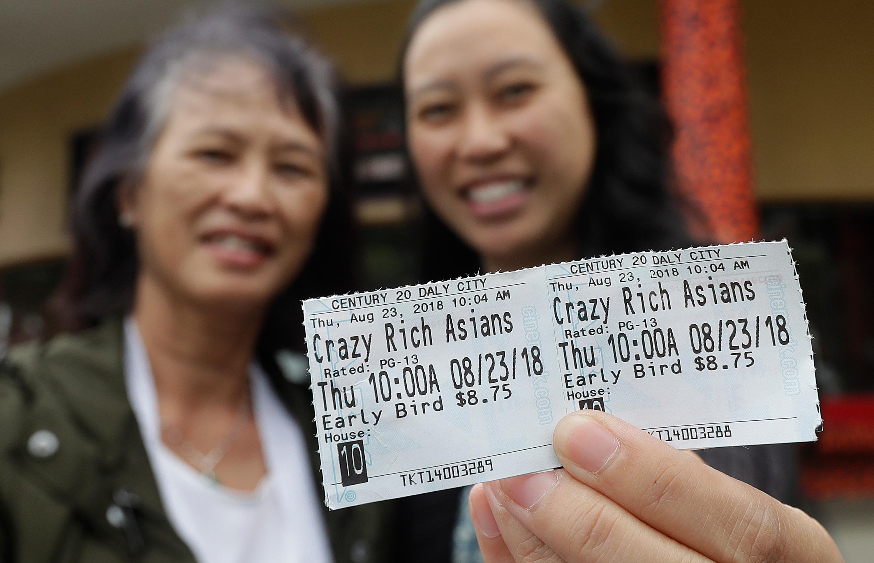 In this Thursday, Aug. 23, 2018 photo, Audrey Sue-Matsumoto, right, holds tickets as she poses for photos with her mother Alice Sue while interviewed outside of a movie theater after watching the movie Crazy Rich Asians in Daly City, Calif. It was Alice Sue's second time watching the movie. (AP Photo/Jeff Chiu)