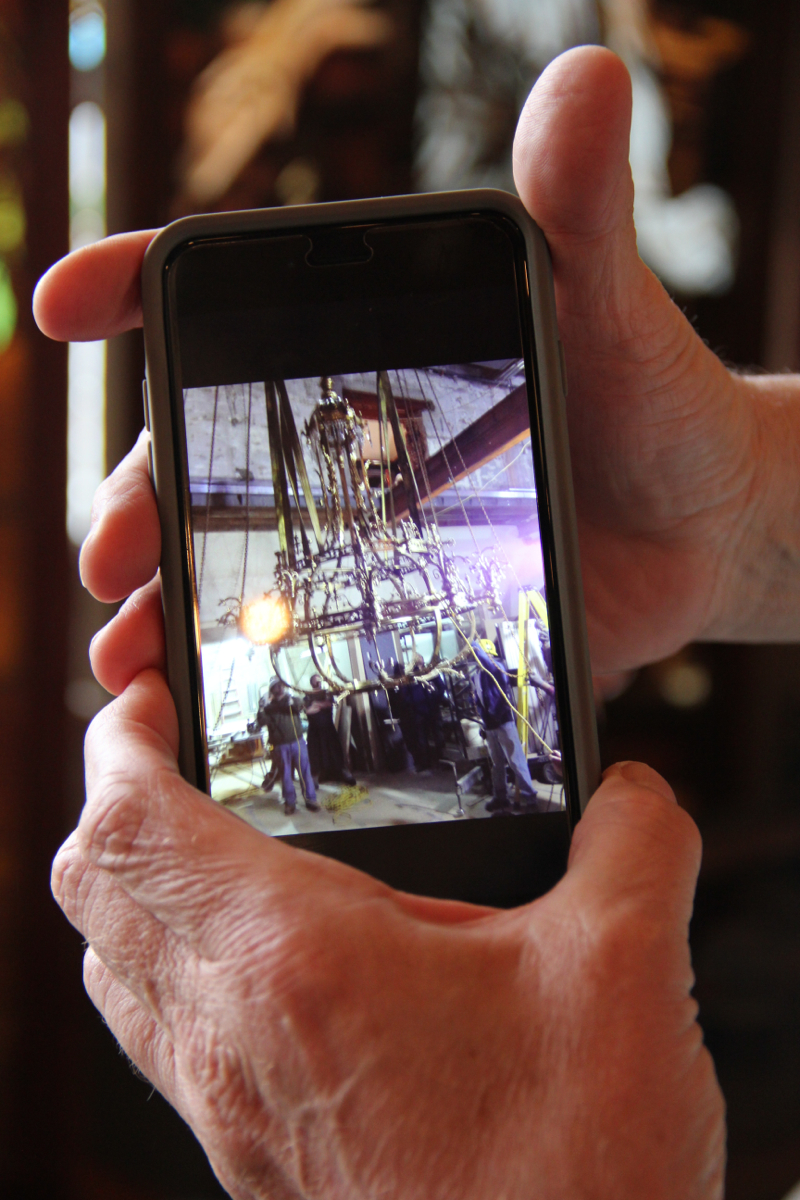 "Mike Williams (co-owner, Wooden Nickel Antiques) showing a picture of the installation-process for  Boca's chandelier -- Rocking the architectural antique scene since 1976, Wooden Nickel specializes in a variety of styles, eras, and furniture genres. Because its real focus is on ""WOW."""
