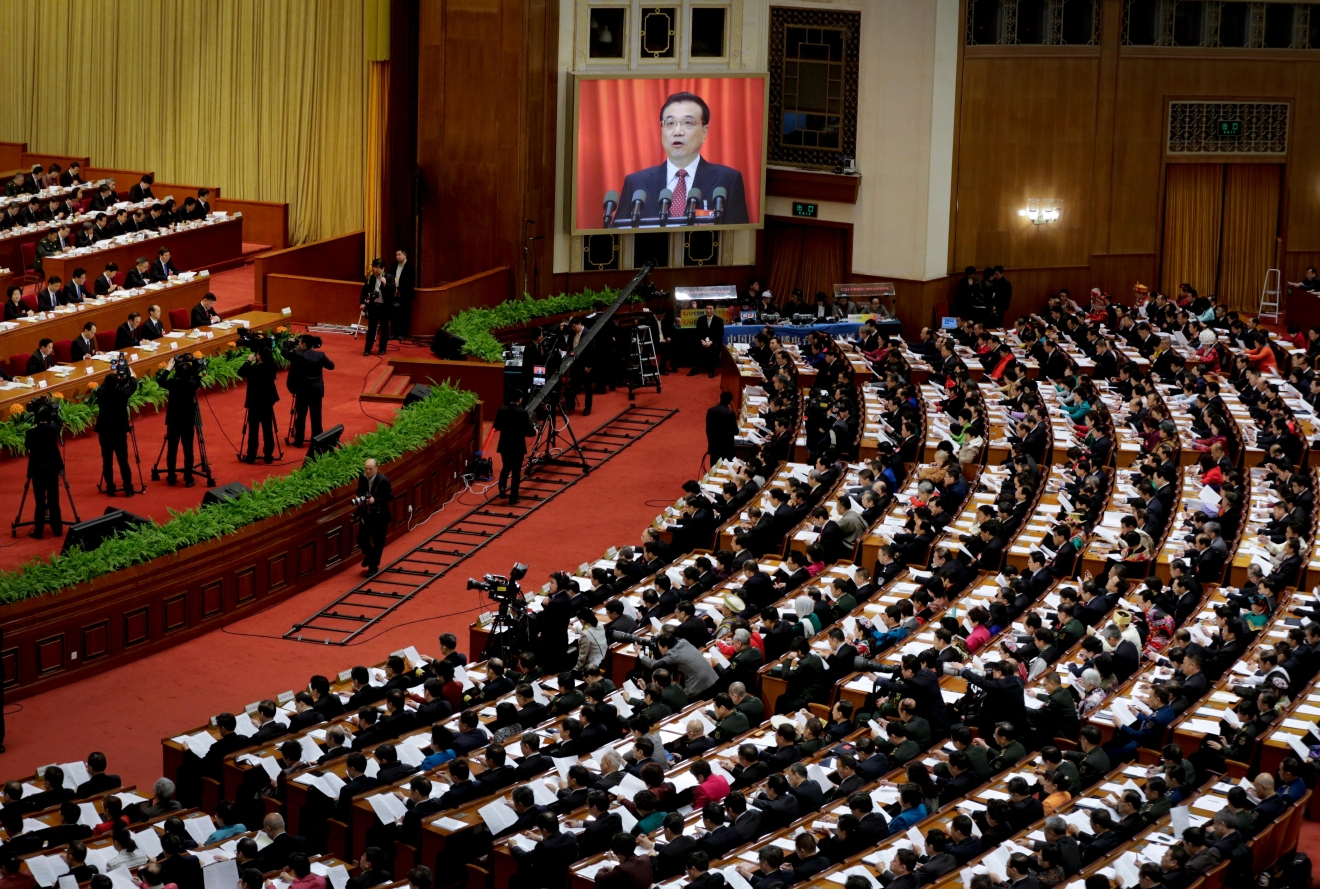 FILE - In this March 5, 2016 file photo, Chinese Premier Li Keqiang appears on a big screen as he delivers a work report at the opening session of the annual National People's Congress at the Great Hall of the People in Beijing. Democracy Chinese-style will go on display when the country's rubberstamp legislature, the National People's Congress opens its annual sessions in Beijing on Sunday, March 5, 2017. (AP Photo/Andy Wong, File)