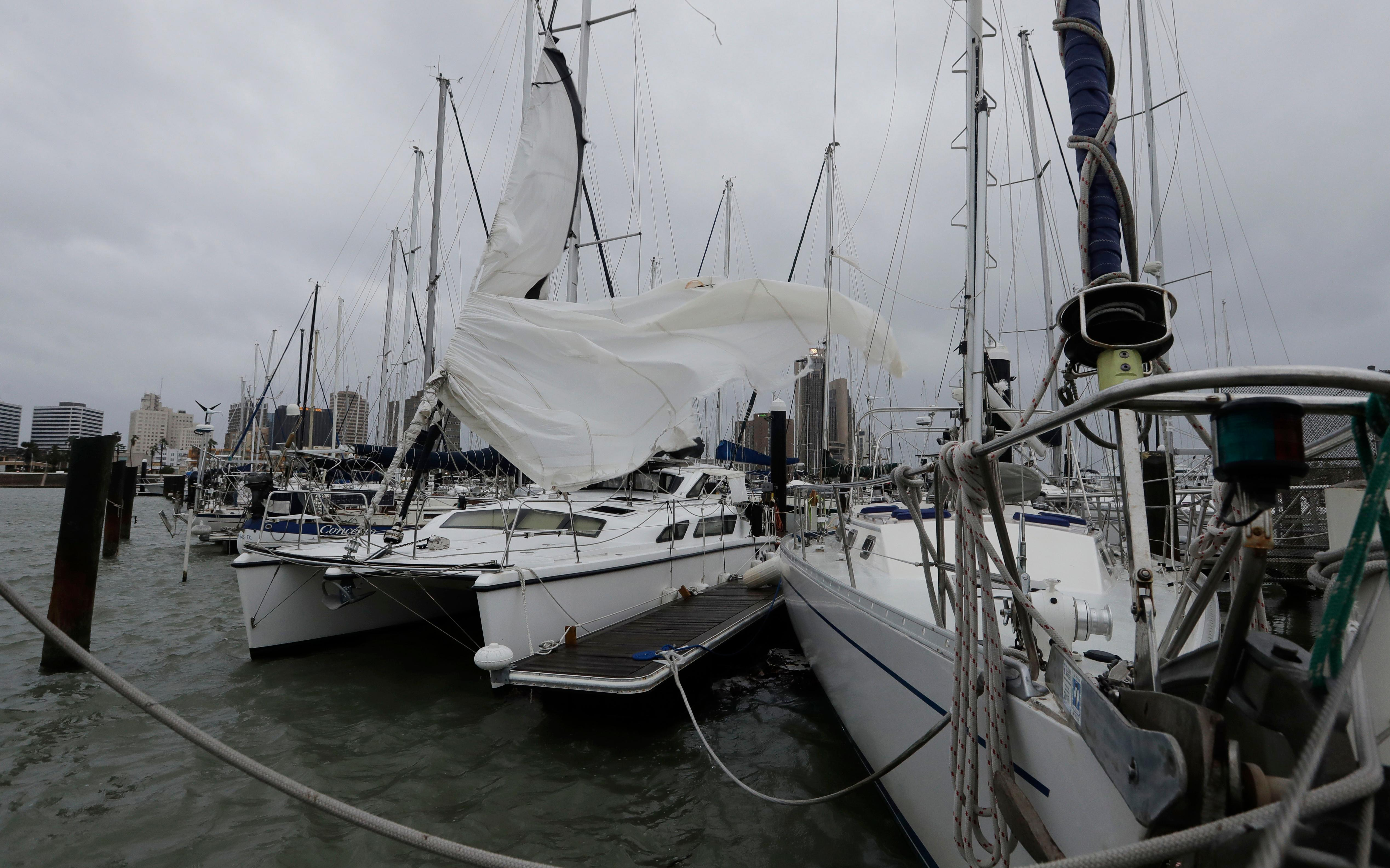 Ripped sails of boats whip in the wind, damaged by Hurricane Harvey, Saturday, Aug. 26, 2017, in Corpus Christi, Texas. Harvey has been further downgraded to a Category 1 hurricane as it churns slowly inland from the Texas Gulf Coast, already depositing more than 9 inches of rain in South Texas.  (AP Photo/Eric Gay)