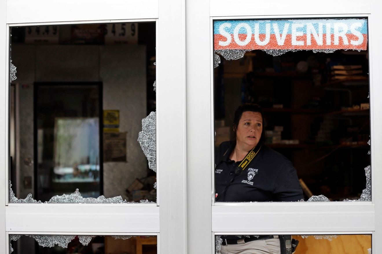 A crime scene photographer looks out a storefront damaged overnight by protesters following Tuesday's police shooting of Keith Lamont Scott in Charlotte, N.C., Thursday, Sept. 22, 2016.  (AP Photo/Gerry Broome)
