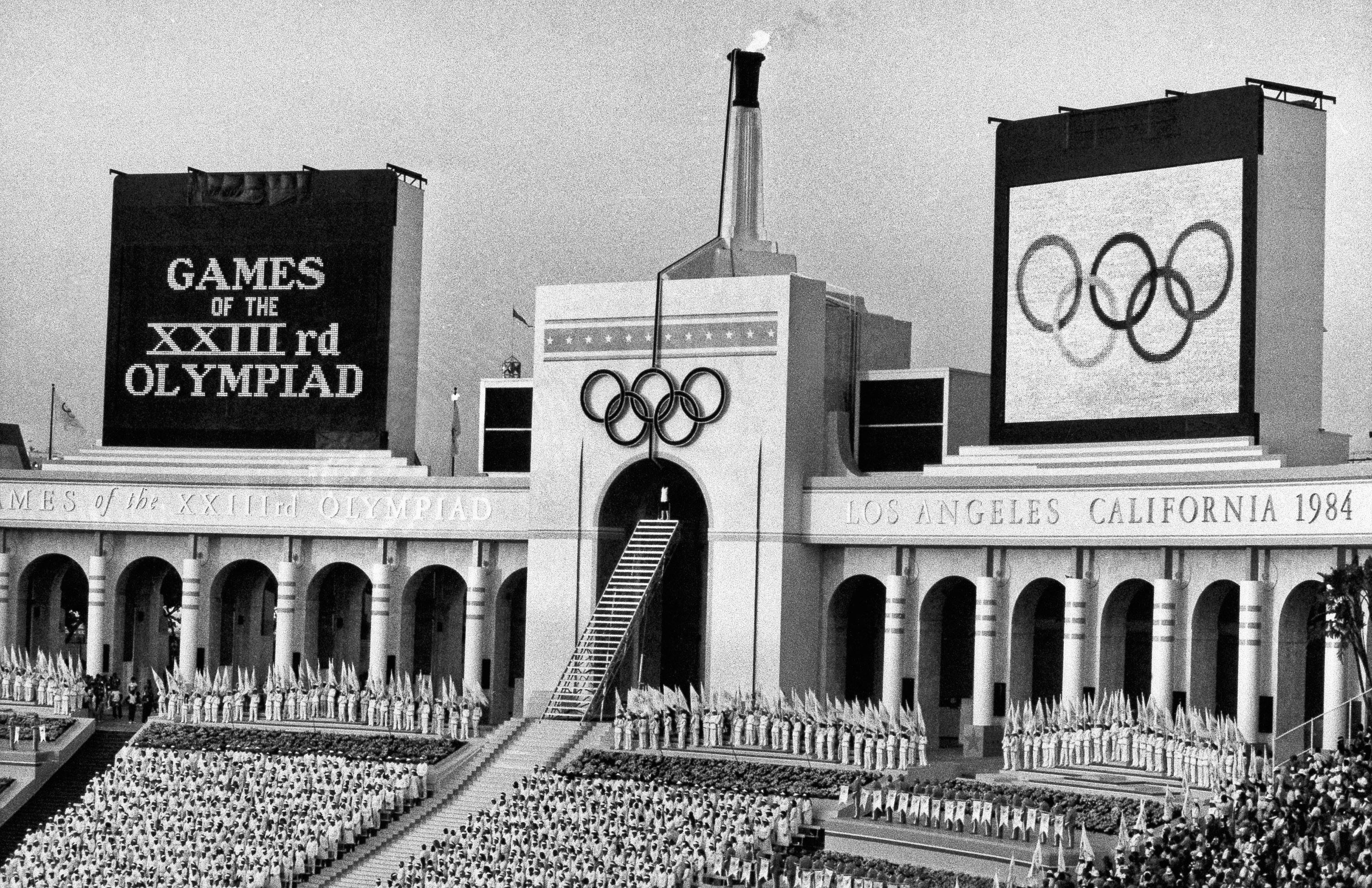 FILE - In this July 28, 1984, file photo, the Olympic flame is flanked by a scoreboard signifying the formal opening of the XXIII Olympiad after it was lit by Rafer Johnson during the opening ceremonies in Los Angeles Memorial Coliseum in Los Angels. (AP Photo/Eric Risberg, File)