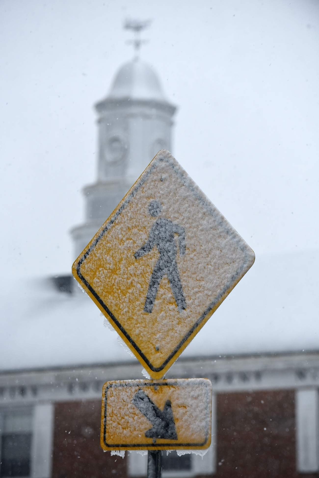 Snow sticks to a pedestrian crossing sign at the Burlington Riverfront Promenade during a snowstorm in Burlington City on Wednesday, March 7, 2018. [CARL KOSOLA / STAFF PHOTOJOURNALIST]