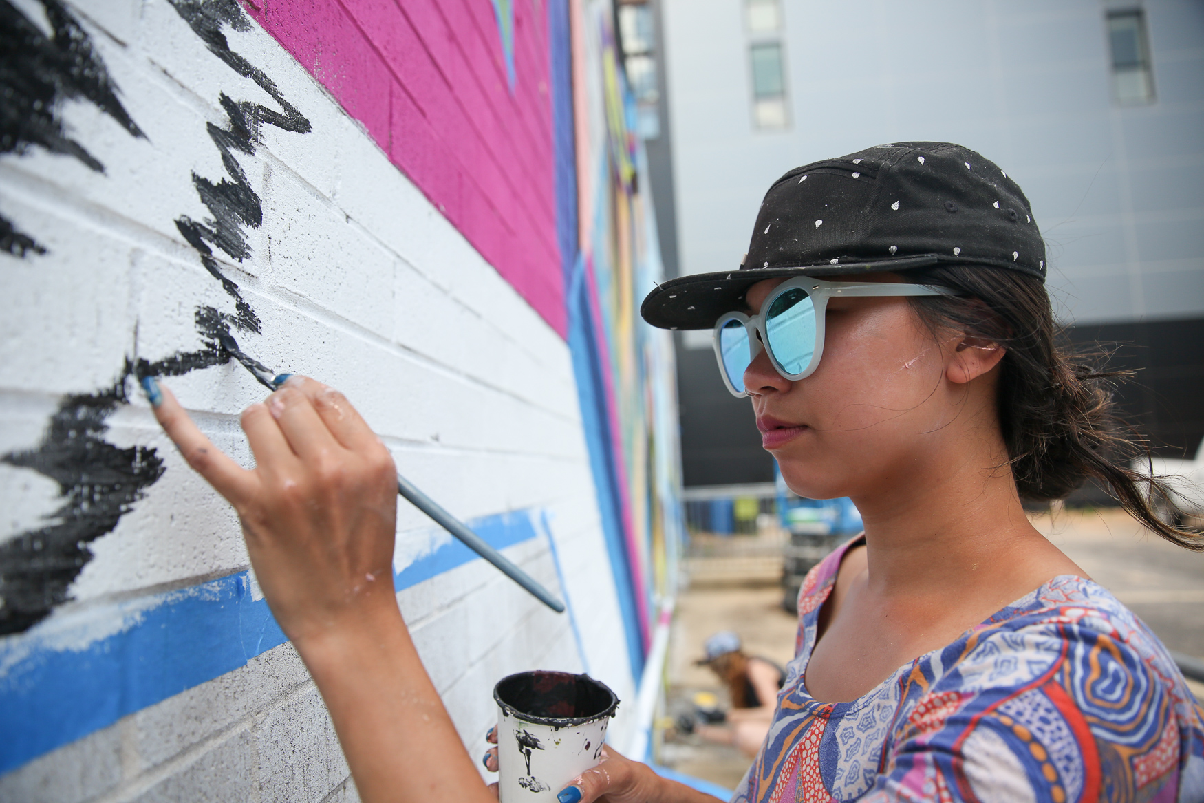 Priscilla Yu of Vancouver, Canada, works on her mural on Patterson St. NE, between{ } (Amanda Andrade-Rhoades/DC Refined)