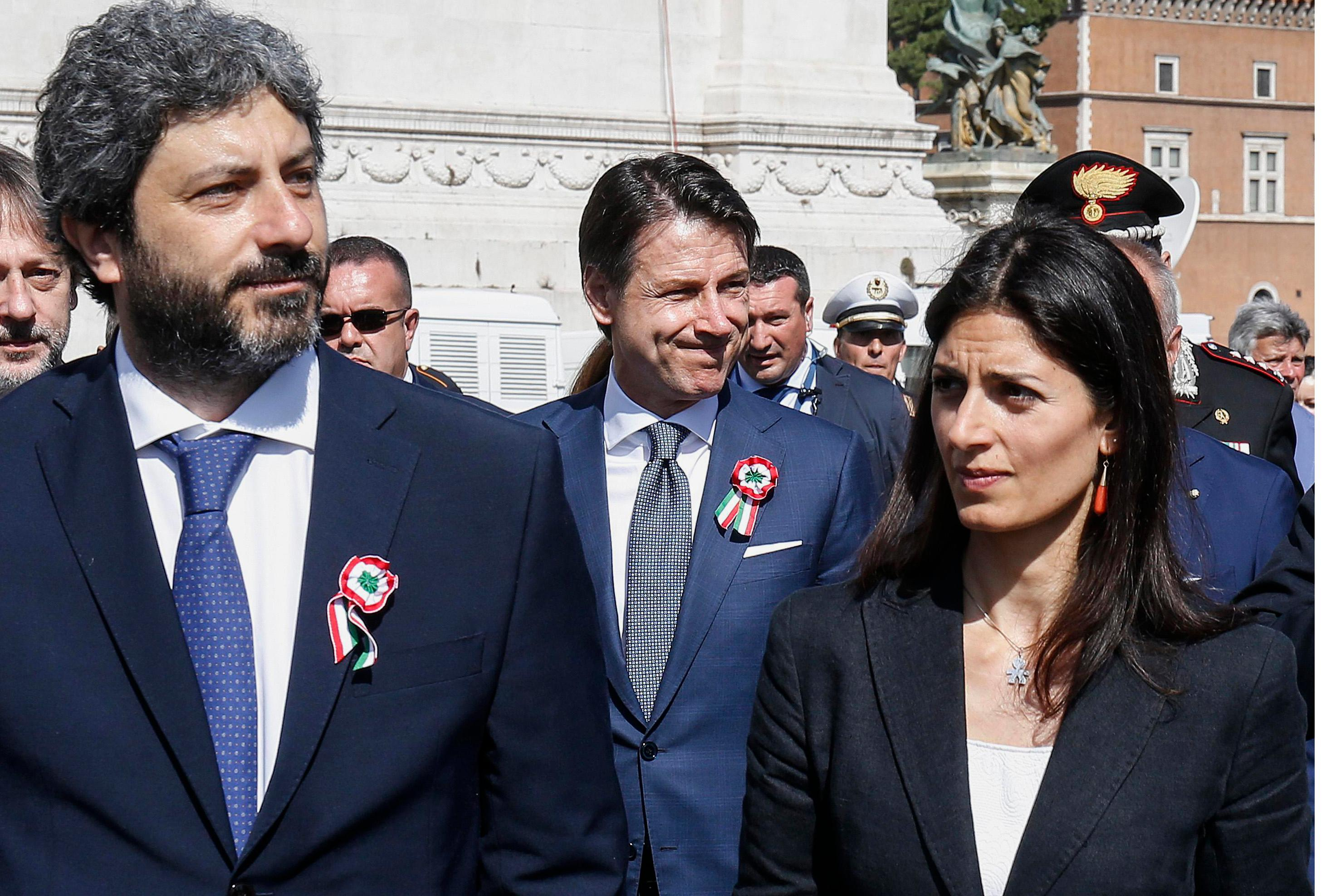 Italian Premier Giuseppe Conte, center, is flanked by Roberto Fico, left, president of the Lower Chamber, and Rome's Mayor Virginia Raggi, on the occasion of celebrations for Italy's Republic Day, in Rome Saturday, June 2, 2018. (Fabio Frustaci/ANSA via AP)