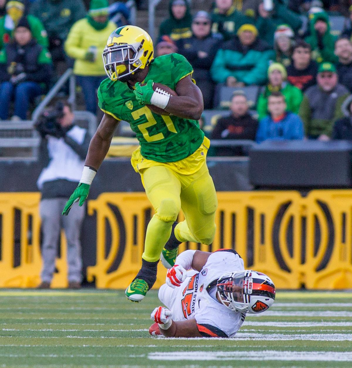 Oregon Ducks Royce Freeman (#21) leaps over Oregon State Beaver Manase Hungalo (#55) during the second half. The Oregon Ducks beat the Oregon State Beavers 52-42 in the 119th Civil War for the eighth year in a row at Autzen Stadium on Friday afternoon. Katie Pietzold, Oregon News Lab