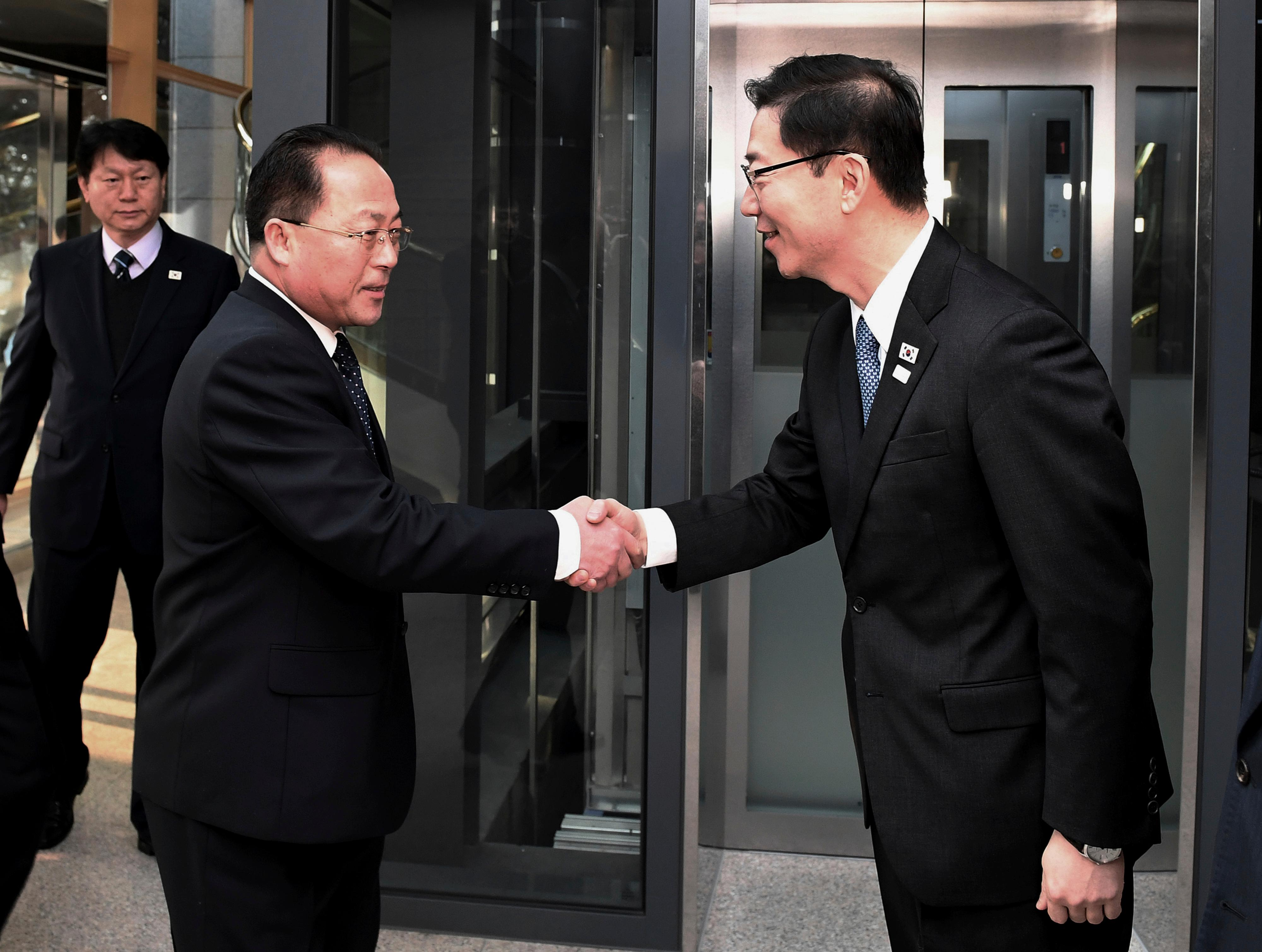 In this photo provided by South Korea Unification Ministry, South Korean Vice Unification Minister Chun Hae-sung, right, shakes hands with the head of North Korean delegation Jon Jong Su before their meeting at Panmunjom in the Demilitarized Zone in Paju, South Korea, Wednesday, Jan. 17, 2018. The two Koreas are meeting Wednesday for the third time in about 10 days to continue their discussions on Olympics cooperation, days ahead of talks with the IOC on North Korean participation in the upcoming Winter Games in the South. (South Korea Unification Ministry via AP)