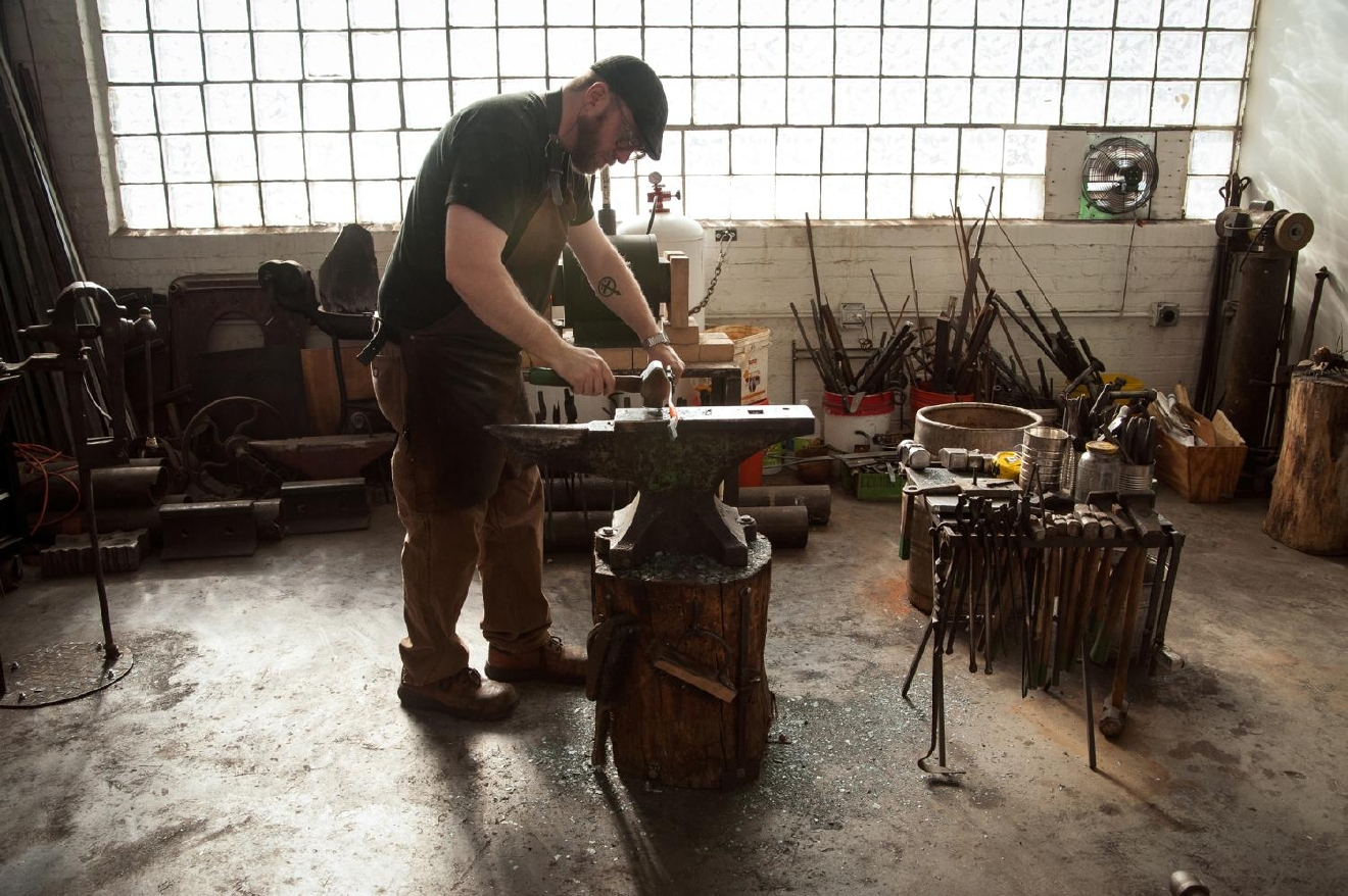 Mark Gilsdorf, Artist-Blacksmith, works in his studio. Gilsdorf began learning the craft in 2007 and became a full-time blacksmith in 2013. Aside from commissions, he sells his creations at Bromwells and local events, such as Summerfair and the Hyde Park Art Show. / Image: Melissa Doss Sliney