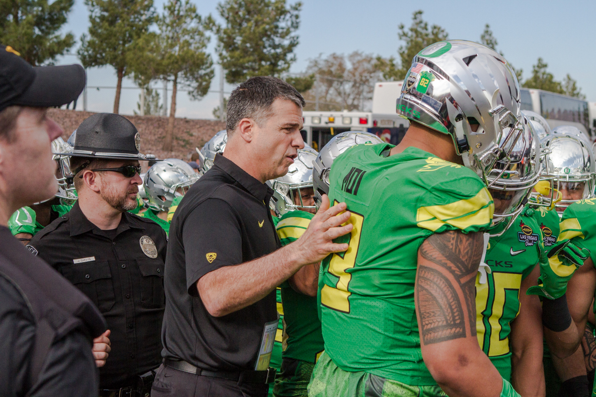 New Oregon Head Coach Mario Cristobal talks with players before kickoff. The Boise State Broncos defeated the Oregon Ducks 38 to 28 in the 2017 Las Vegas Bowl at Sam Boyd Stadium in Las Vegas, Nevada on Saturday December 17, 2017. The Las Vegas Bowl served as the first test for Oregon's new Head Coach Mario Cristobal following the loss of former Head Coach Willie Taggart to Florida State University earlier this month. Photo by Ben Lonergan, Oregon News Lab