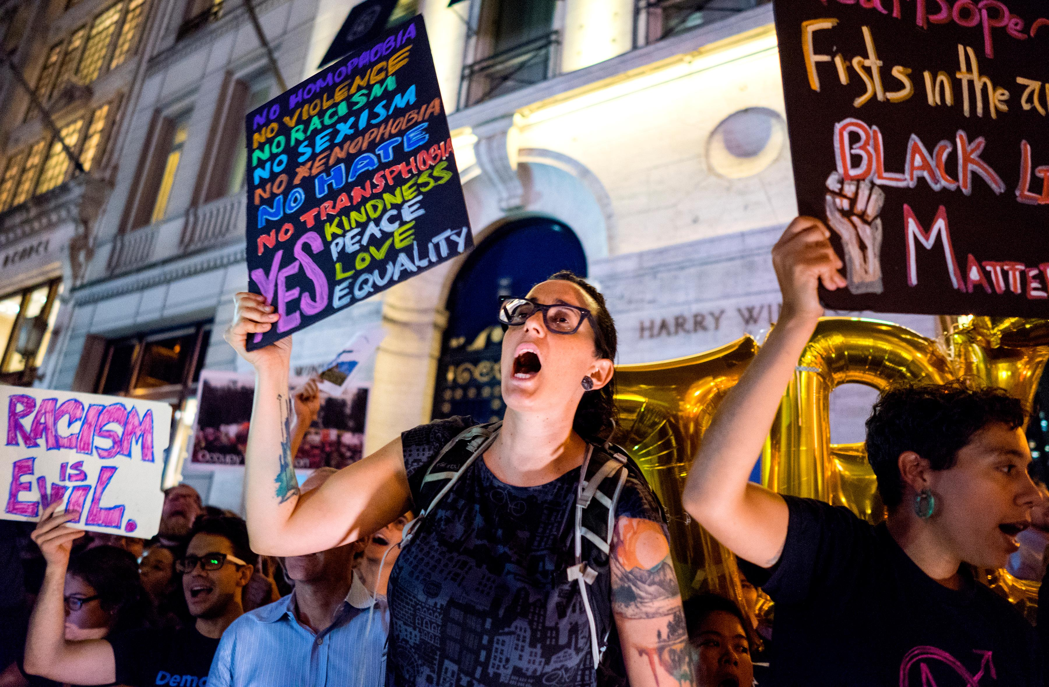 Protestors near Trump Tower react as President Donald Trump arrives, Monday, Aug. 14, 2017, in New York. (AP Photo/Craig Ruttle)