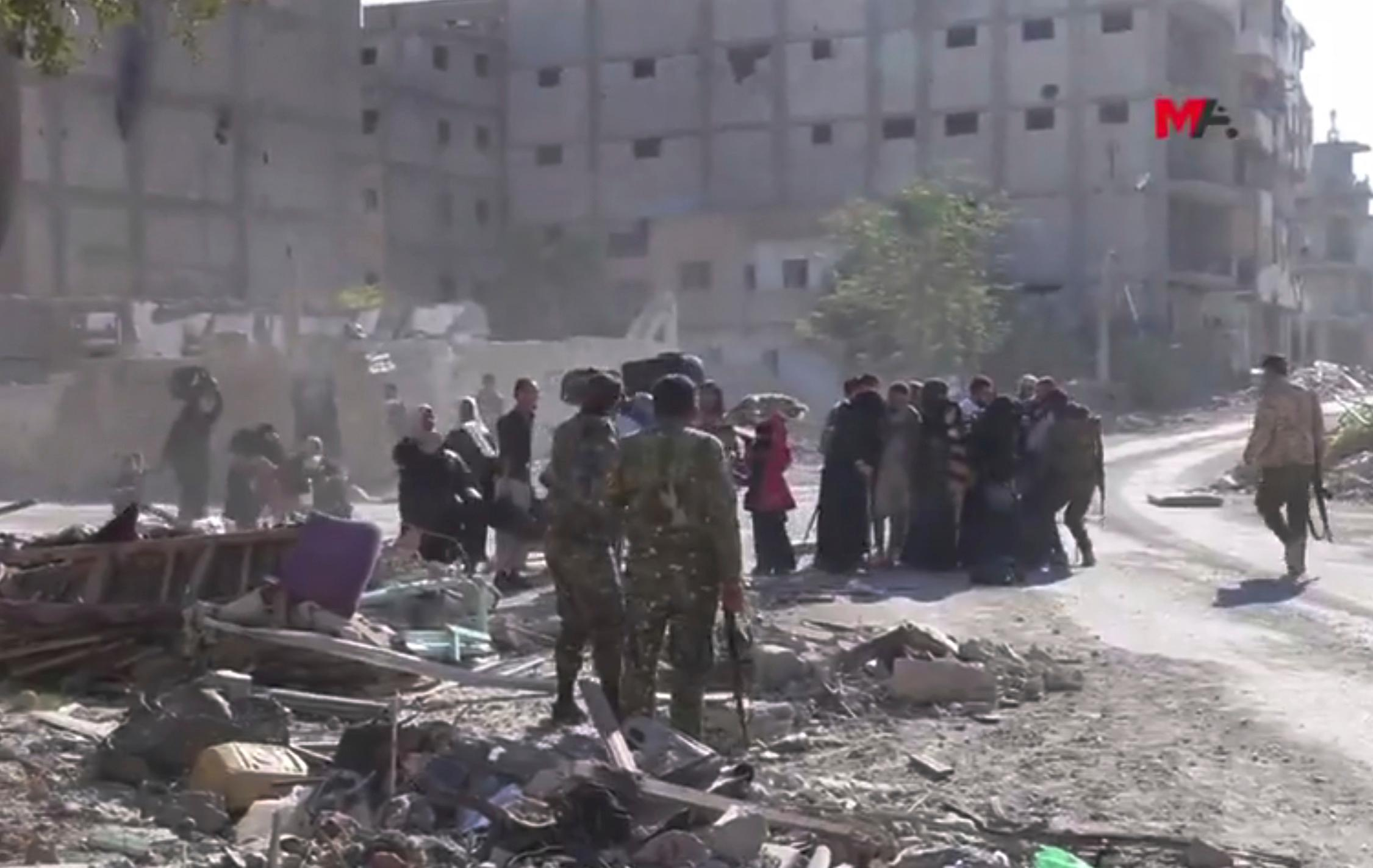 This frame grab from a video provided on Friday, Oct. 13, 2017 by Turkey-based Kurdish Mezopotamya agency media outlet that is consistent with independent AP reporting, shows U.S.-backed Syrian Democratic Forces (SDF) fighters, stand around Syrian civilians who fled from the areas that still controlled by the Islamic State militants, in Raqqa, Syria. Scores of civilians including women and children are fleeing the last few remaining neighborhoods held by the Islamic State group in Syria's northern city of Raqqa, ahead of an anticipated final push by U.S.-backed fighters seeking to liberate the city. (Mezopotamya Agency, via AP)