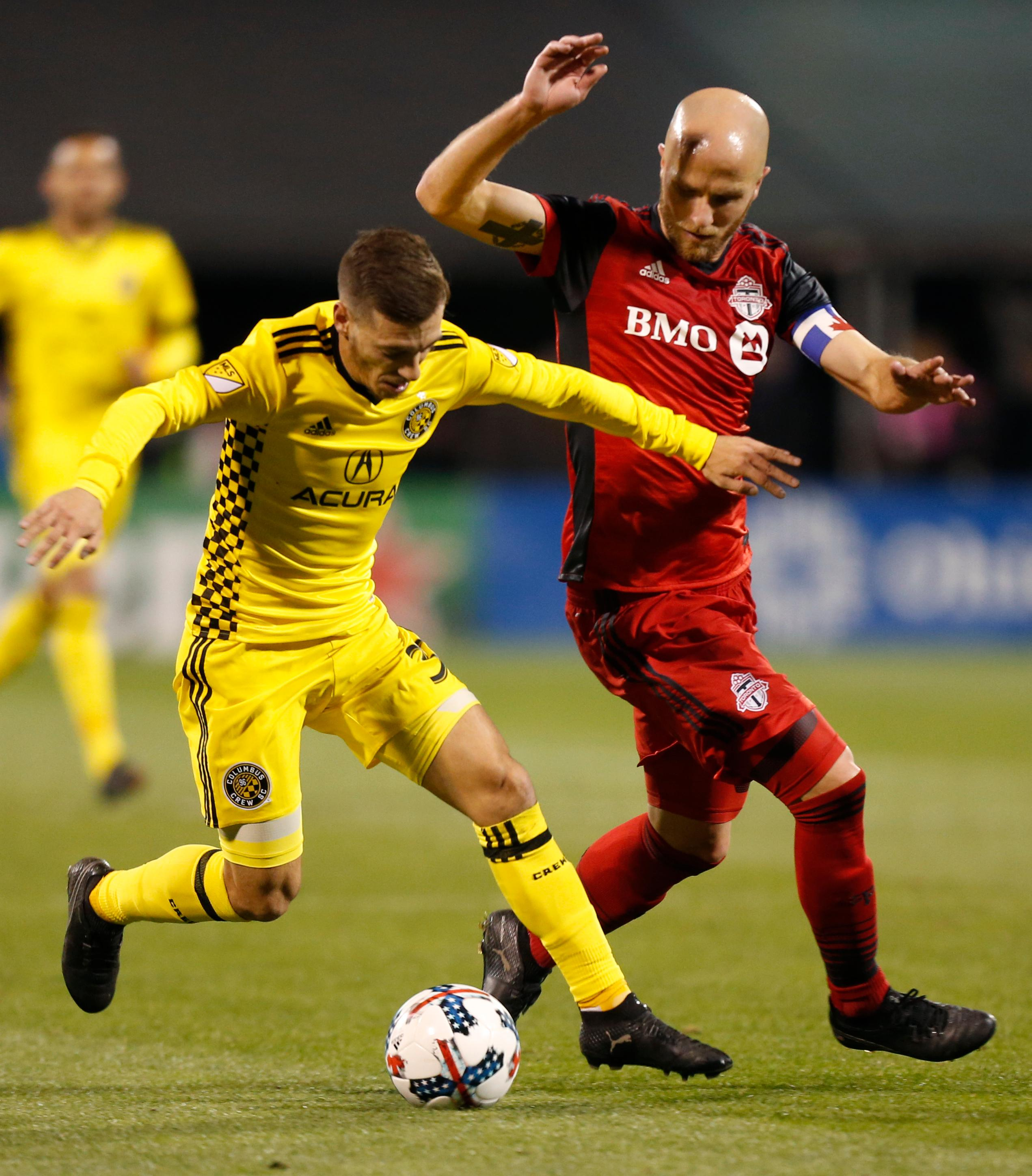 Columbus Crew's Pedro Santos, left, keeps the ball away from Toronto FC's Michael Bradley during the first half of an MLS Eastern Conference championship soccer match Tuesday, Nov. 21, 2017, in Columbus, Ohio. (AP Photo/Jay LaPrete)