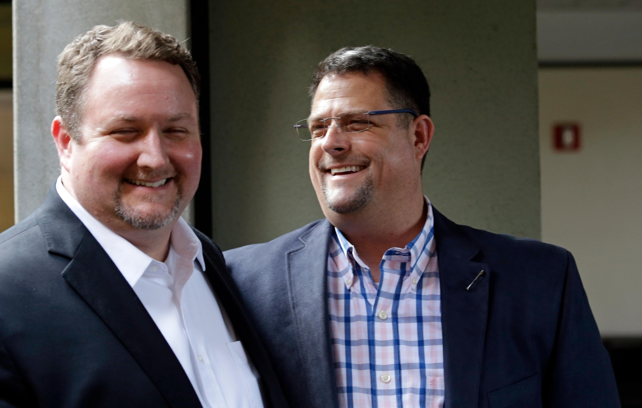 Curt Freed, left, and his husband Robert Ingersoll smile after a hearing before Washington's Supreme Court, Tuesday, Nov. 15, 2016, in Bellevue, Wash. The couple sued florist Barronelle Stutzman for refusing to provide services for their wedding,  Stutzman says she was exercising her First Amendment rights, but justices questioned whether ruling in her favor would mean other businesses could turn away customers based on racial or other grounds. (AP Photo/Elaine Thompson)