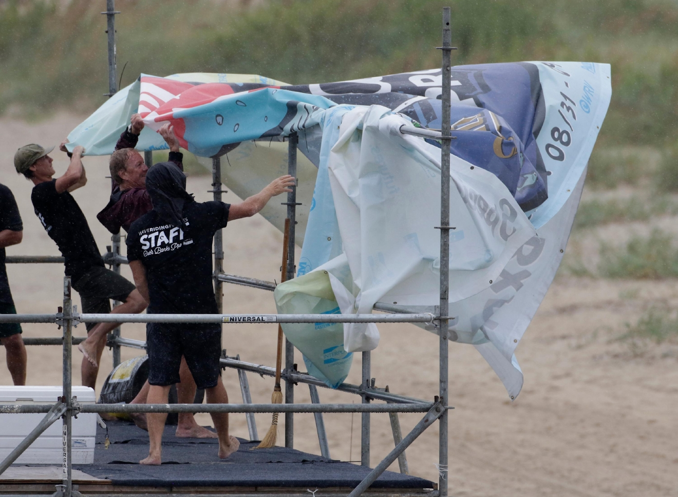 Staff members for the MRV Outer Banks Pro surf tournament take down a banner in Nags Head, N.C., Friday, Sept. 2, 2016, as Tropical Storm Hermine heads toward the Outer Banks. (AP Photo/Tom Copeland)