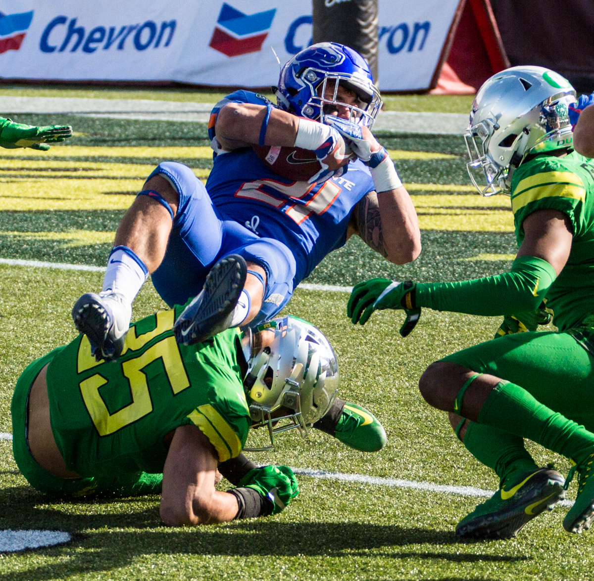 Boise State running back Ryan Wolpin (#21) falls over an Oregon defender. The Boise State Broncos defeated the Oregon Ducks 38 to 28 in the 2017 Las Vegas Bowl at Sam Boyd Stadium in Las Vegas, Nevada on Saturday December 17, 2017. The Las Vegas Bowl served as the first test for Oregon's new Head Coach Mario Cristobal following the loss of former Head Coach Willie Taggart to Florida State University earlier this month. Photo by Ben Lonergan, Oregon News Lab