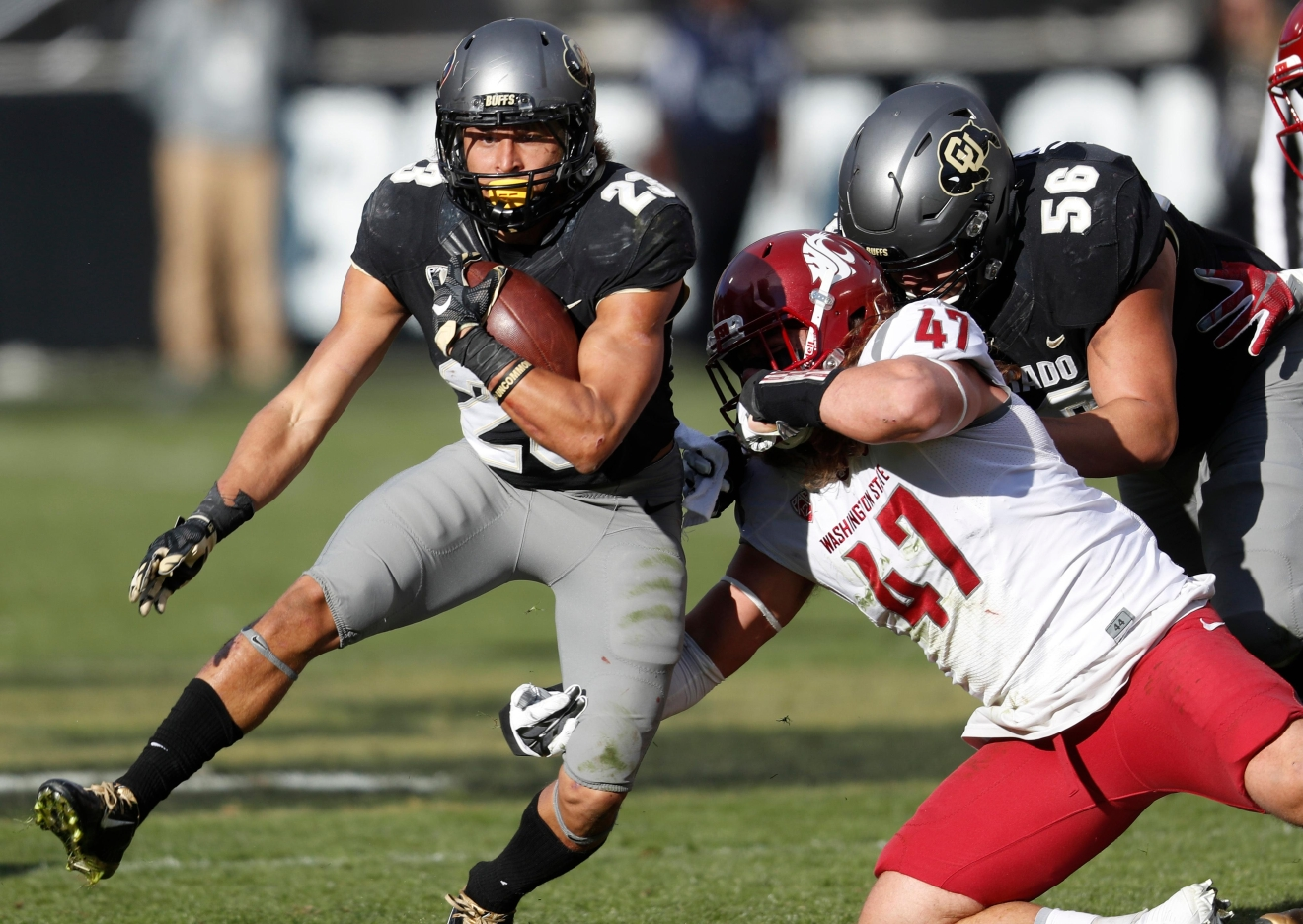 Colorado running back Phillip Lindsay, left, is pulled down by Washington State linebacker Peyton Pelluer in the first half of an NCAA college football game, Saturday, Nov. 19, 2016, in Boulder, Colo. (AP Photo/David Zalubowski)