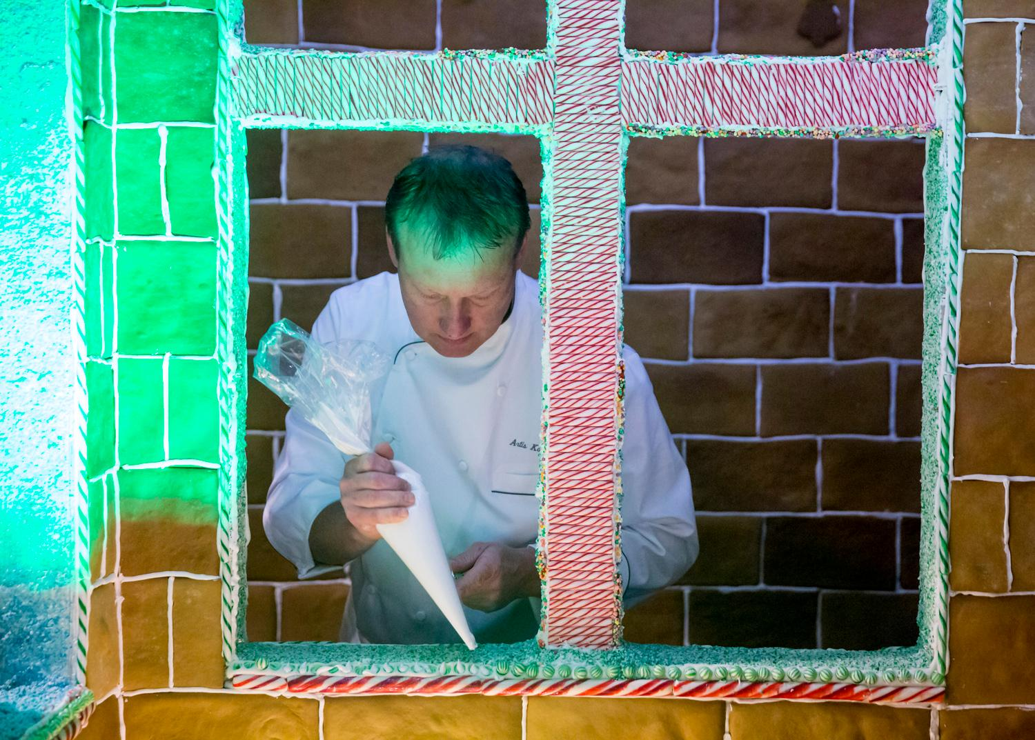 Executive pastry chef Artis Kalsons replaces candies on his lifesize gingerbread house after hungry kids picked them off at the entrance of the Fairmount Olympic Hotel in downtown Seattle. Talk about a dream home! Well - for a person with a sweet tooth that is! The creation of this colossal Gingerbread house has been going on since August and took eight engineers, 15 culinary stars, and hundreds of helping hands. The recipe looks like this: 960 pounds of flour, 20 gallons of milk, 75 gallons of icing, 80 pounds of molasses, 80 pounds of butter, 3 pounds of cinnamon, 3 pounds of nutmeg, 170 pounds of brown sugar, 3 pounds of anise, and 3 pounds of clove! Phew. It gets better... The finished product has 4,100 Gingerbread tiles, 2,500 candy canes, 1,000 spearmints, 50 pounds of crushed candy and 144 feet of candy ropes. I think we just got a sugar contact high. If you haven't ventured down there, this gingerbread house in a must-see, folks! (Image: Sy Bean / Seattle Refined).