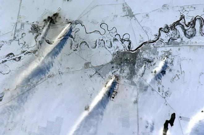 Hot smokestack exhaust streams in the harsh wind across a central Asian winter landscape.  (Photo & Caption: Col. Chris Hadfield, NASA)