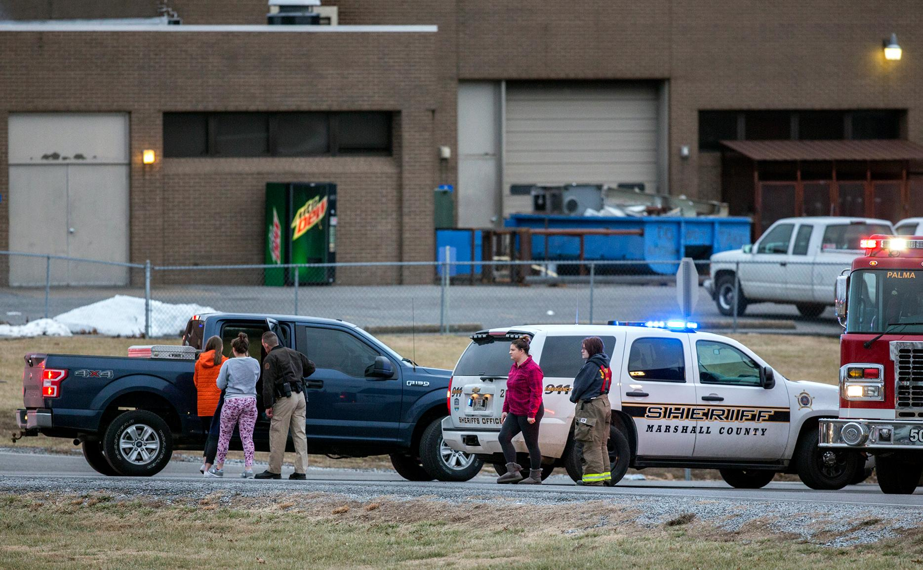 Marshall County High School students are escorted to retrieve their vehicles by emergency responders after a deadly shooting at the school in Benton, Ky., Tuesday, Jan. 23, 2018. (Ryan Hermens/The Paducah Sun via AP)