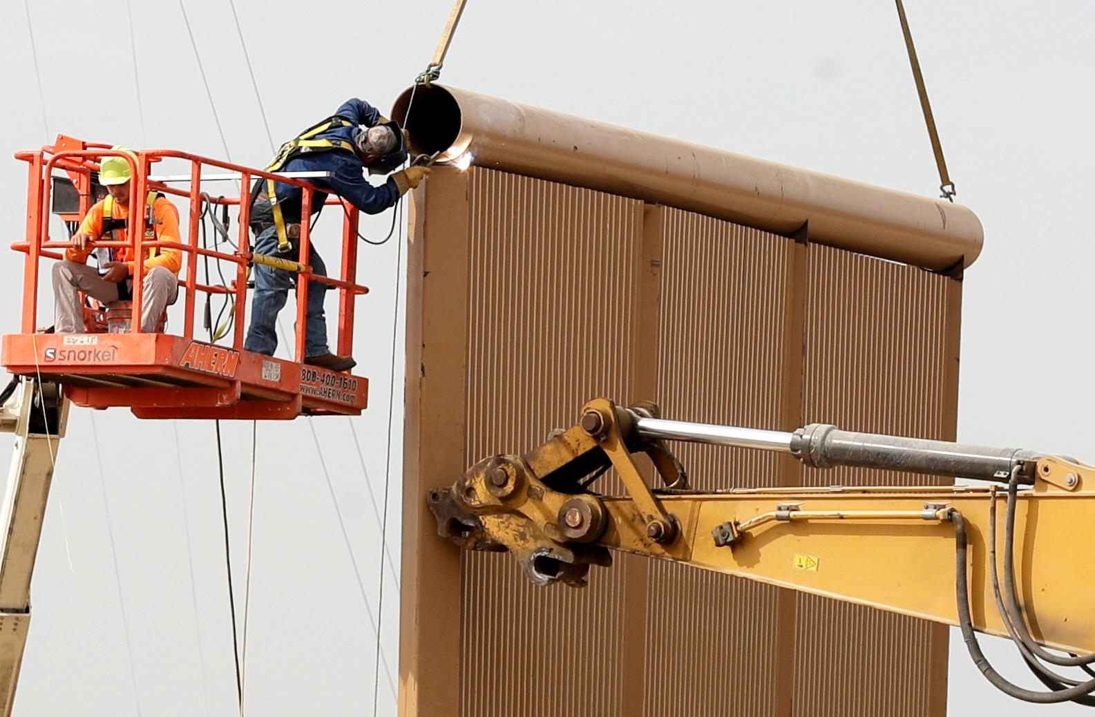 Crews work on a border wall prototype near the border with Tijuana, Mexico, Thursday, Oct. 19, 2017, in San Diego. Companies are nearing an Oct. 26 deadline to finish building eight prototypes of President Donald Trump's proposed border wall with Mexico. (AP Photo/Gregory Bull)