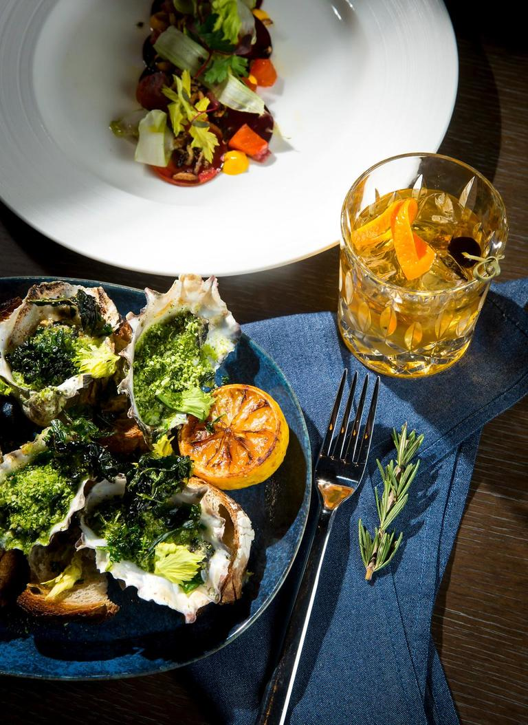 "The Grilled Oysters, presented by executive chef David Nichols, consisting of garlic butter, parsley, and grilled bread, at Rider, located downtown at 619 Pine St. Featured alongside is the C.B.T., which gets its namesake from the 70s soul band featuring ""Kenny G."" Rider draws its inspiration from two of the Pacific Northwest's most defining characteristics - the ocean and the forest - and offers locally sourced dry aged meats, cheeses, and sustainably caught seafood. (Sy Bean / Seattle Refined)"