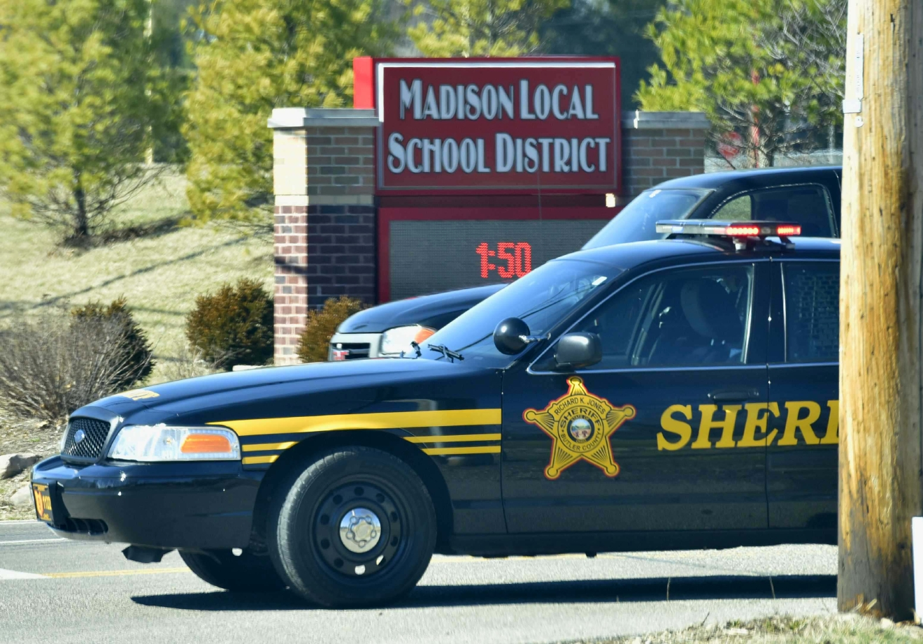 Police vehicles block the entrance of Madison Local Schools, Monday, Feb. 29, 2016, in Madison Township in Butler County, Ohio, after a school shooting. An Ohio sheriff says a 14-year-old suspect in the school shooting that wounded multiple classmates is in custody. (Nick Graham/Dayton Daily News via AP)