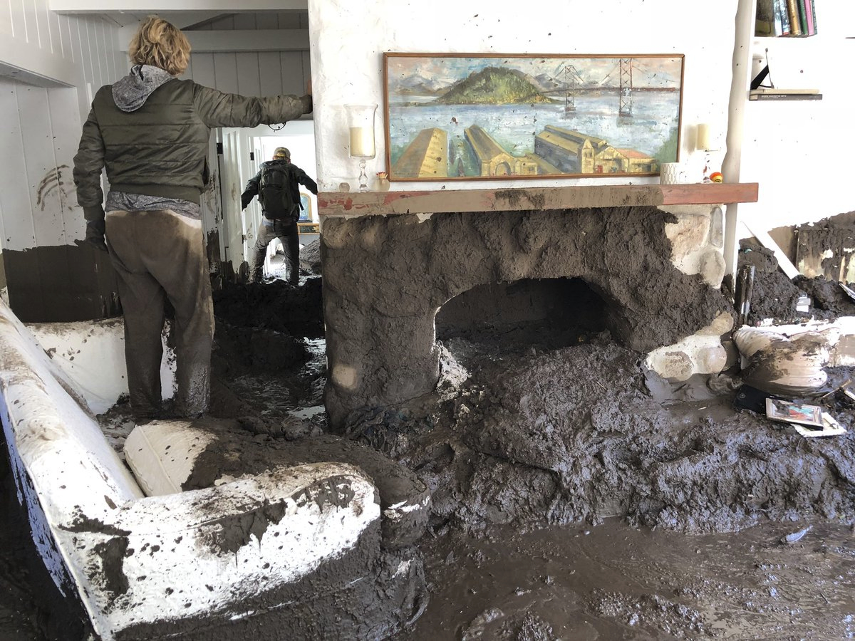 In this photo provided by Santa Barbara County Fire Department, Teresa Drenick stands in her sister's home damaged after heavy rains off Glen Oaks Lane, while Sean Bornwell retrieves some of her sister's personal belongings on Wednesday, Jan. 10, 2018, in Montecito, Calif. Drenick's sister has been missing since early Tuesday morning. Flash floods there on Tuesday swept immense amounts of mud, water and debris down from foothills that were stripped of brush by the recent Thomas wildfire. (Mike Eliason/Santa Barbara County Fire Department via AP)