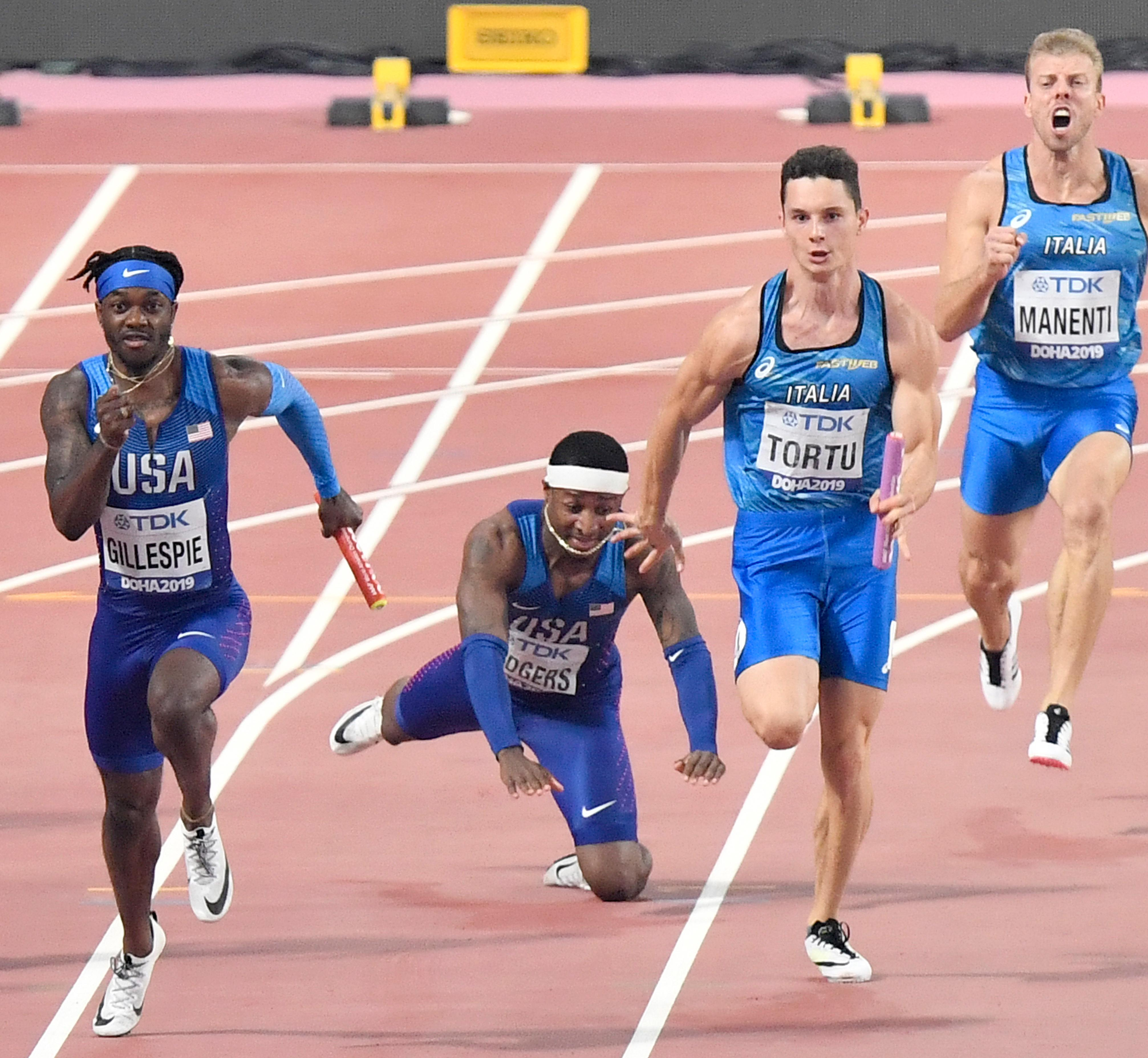 Unites States' Michael Rodgers falls, after relaying with Cravon Gillespie, left, as Italy's Davide Manenti, right screaming, and Filippo Tortu, second right, compete during the men's 400 meter relay at the World Athletics Championships in Doha, Qatar, Friday, Oct. 4, 2019. (AP Photo/Martin Meissner)