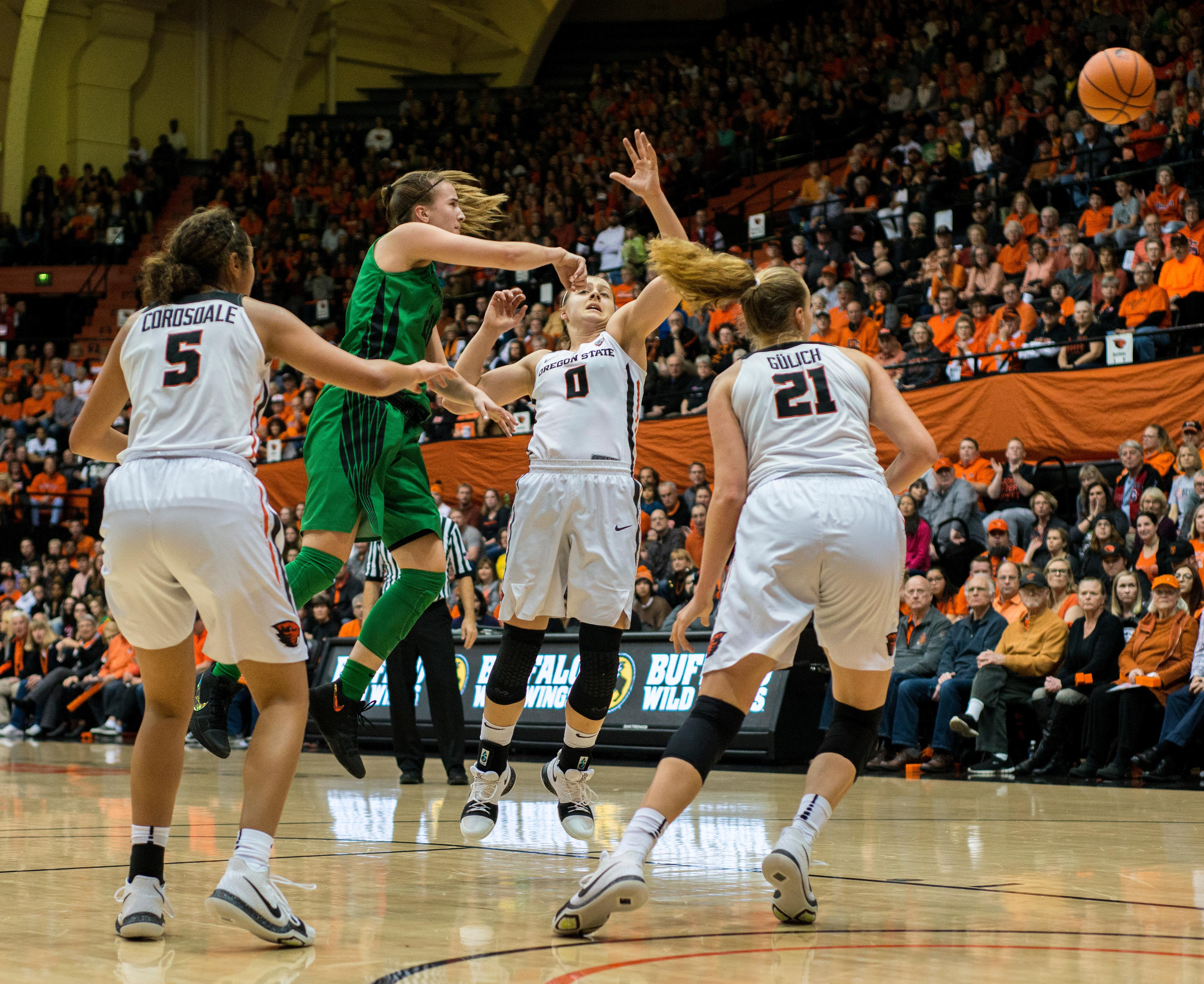 Oregon Ducks guard Sabrina Ionescu (#20) passes hard and fast as Oregon State Beavers guard Mikayla Pivec (#0) dodges the ball.The Oregon Ducks were defeated by the Oregon State Beavers 85-79 on Friday night in Corvallis. Sabrina Ionescu scored 35 points and Ruthy Hebard added 24. The Ducks will face the Beavers this Sunday at 5 p.m. at Matthew Knight Arena. Photo by Abigail Winn, Oregon News Lab
