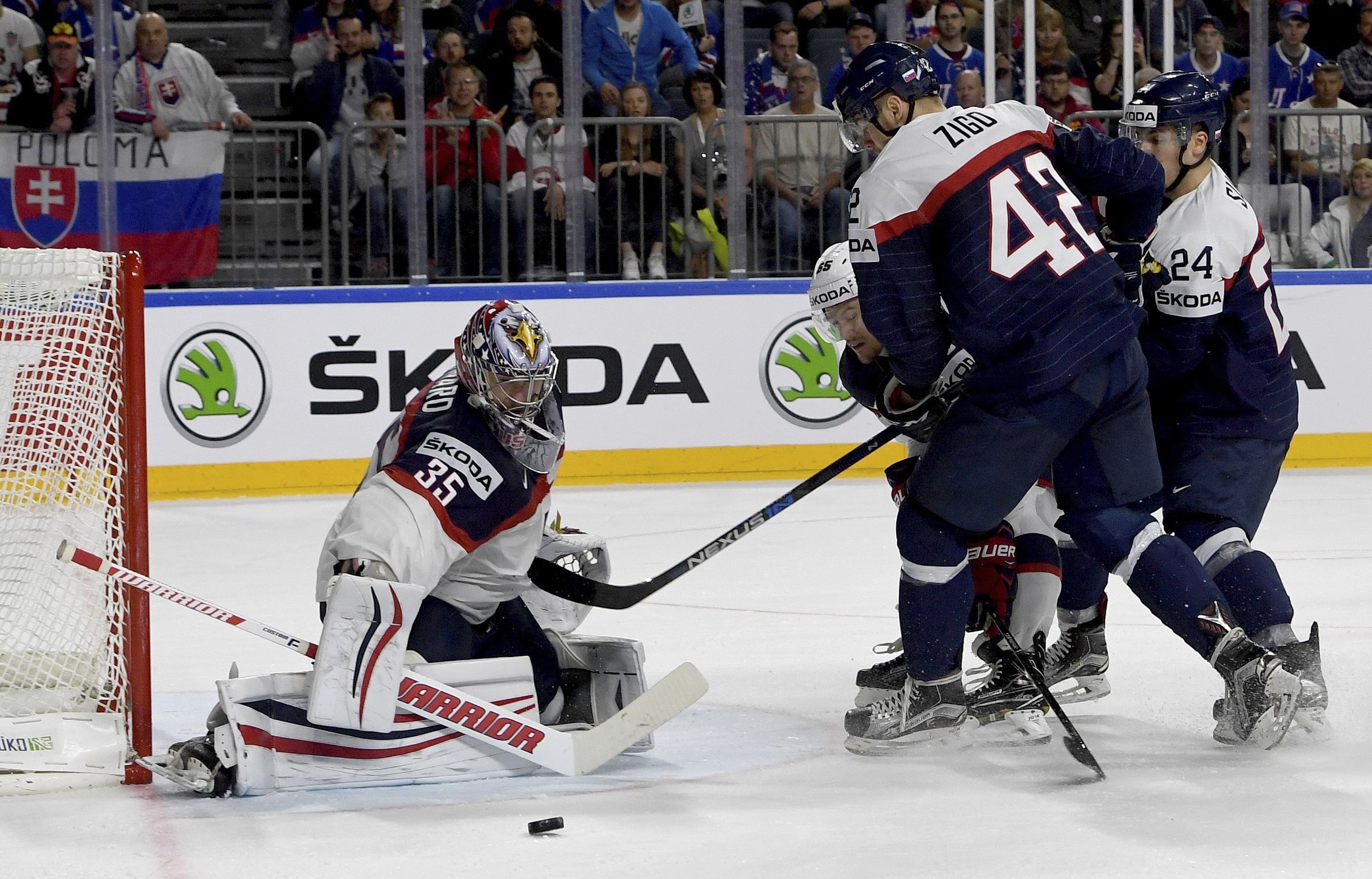 US goalie Jimmy Howard, left,  blocks a shot by Slovakia's Tomas Zigo, second right, during a group A match between Slovakia and USA at the 2017 Hockey World Championships in the Lanxess Arena in  Cologne, Germany, Sunday, May 14, 2017.  (Monika Skolimowska/dpa via AP)