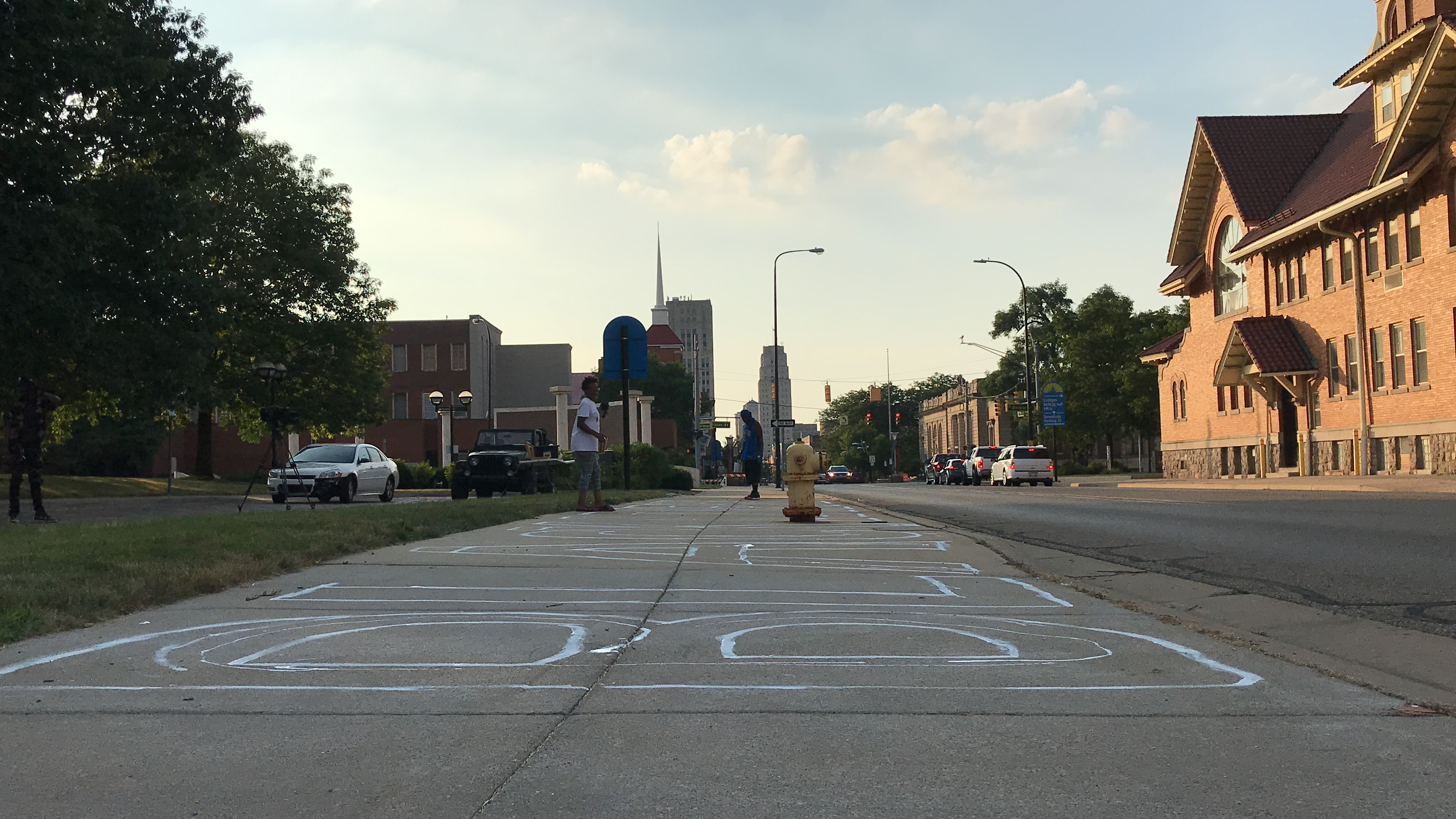 The sun sets on the city, as the Black Lives Matter version of the mural nears completion in Battle Creek, Michigan, on Tuesday, July 7, 2020. Just the outline will be in white. Artists will later fill the letters with color. (WWMT/Jason Heeres)