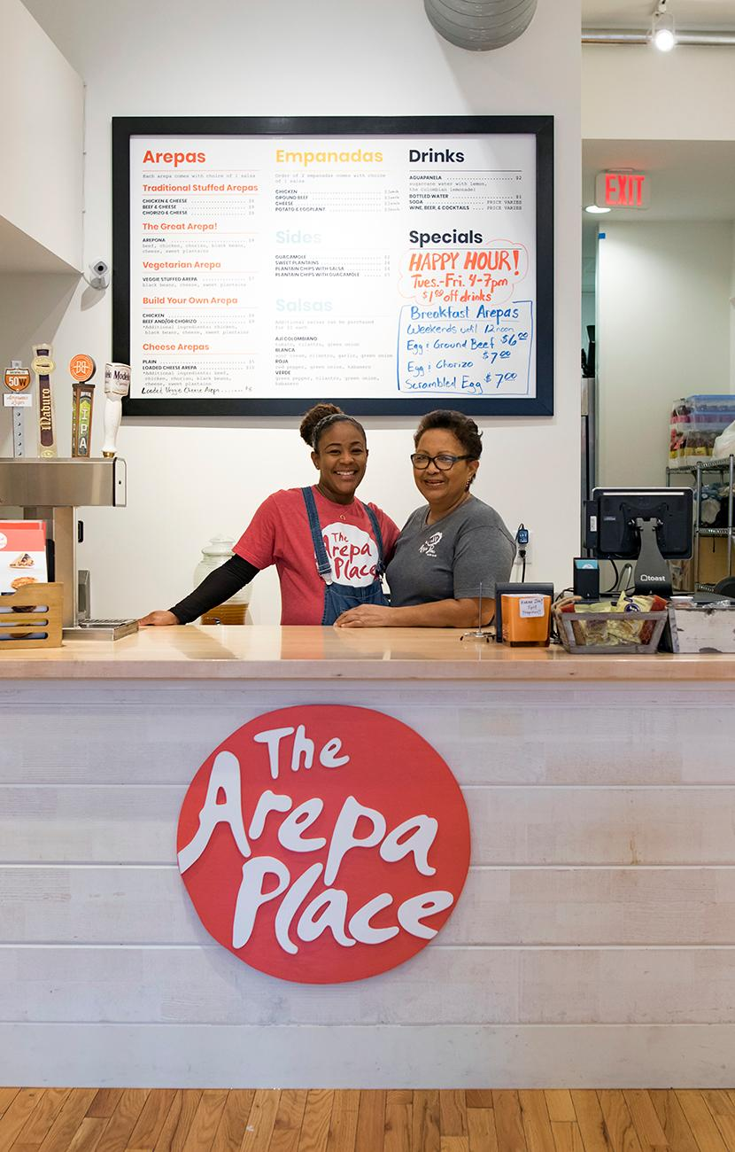 <p>Isis Arrieta-Dennis, owner, and Isis Julio de Arrieta, her mother, do the cooking at The Arepa Place. / Image: Allison McAdams // Published: 3.4.19</p>