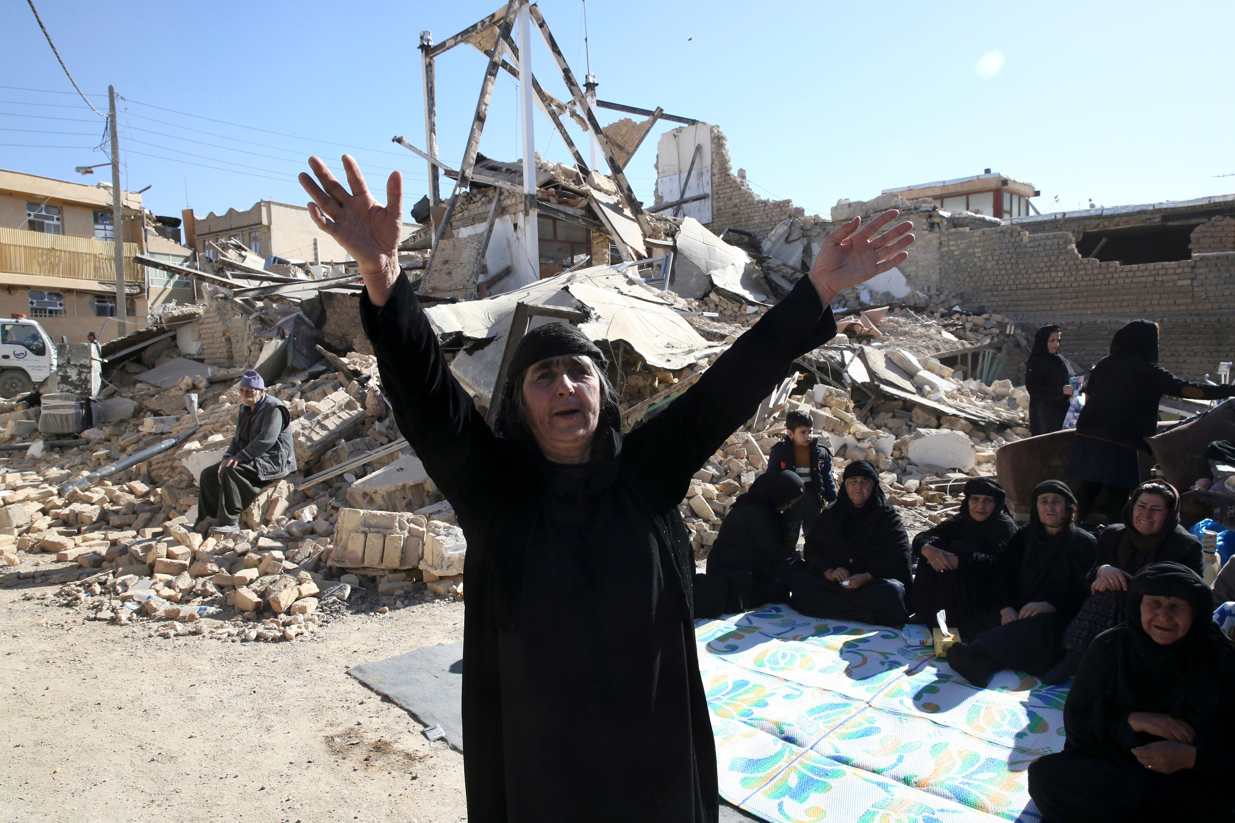 A woman mourns at an earthquake site in Sarpol-e-Zahab in western Iran, Tuesday, Nov. 14, 2017. Rescuers are digging through the debris of buildings felled by the Sunday earthquake in the border region of Iran and Iraq. (AP Photo/Vahid Salemi)