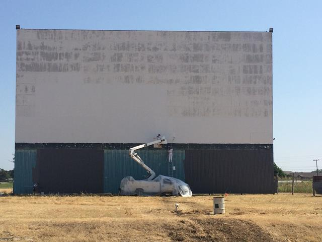 The 60 by 20 foot screen required a new paint job before the movie could be shown.