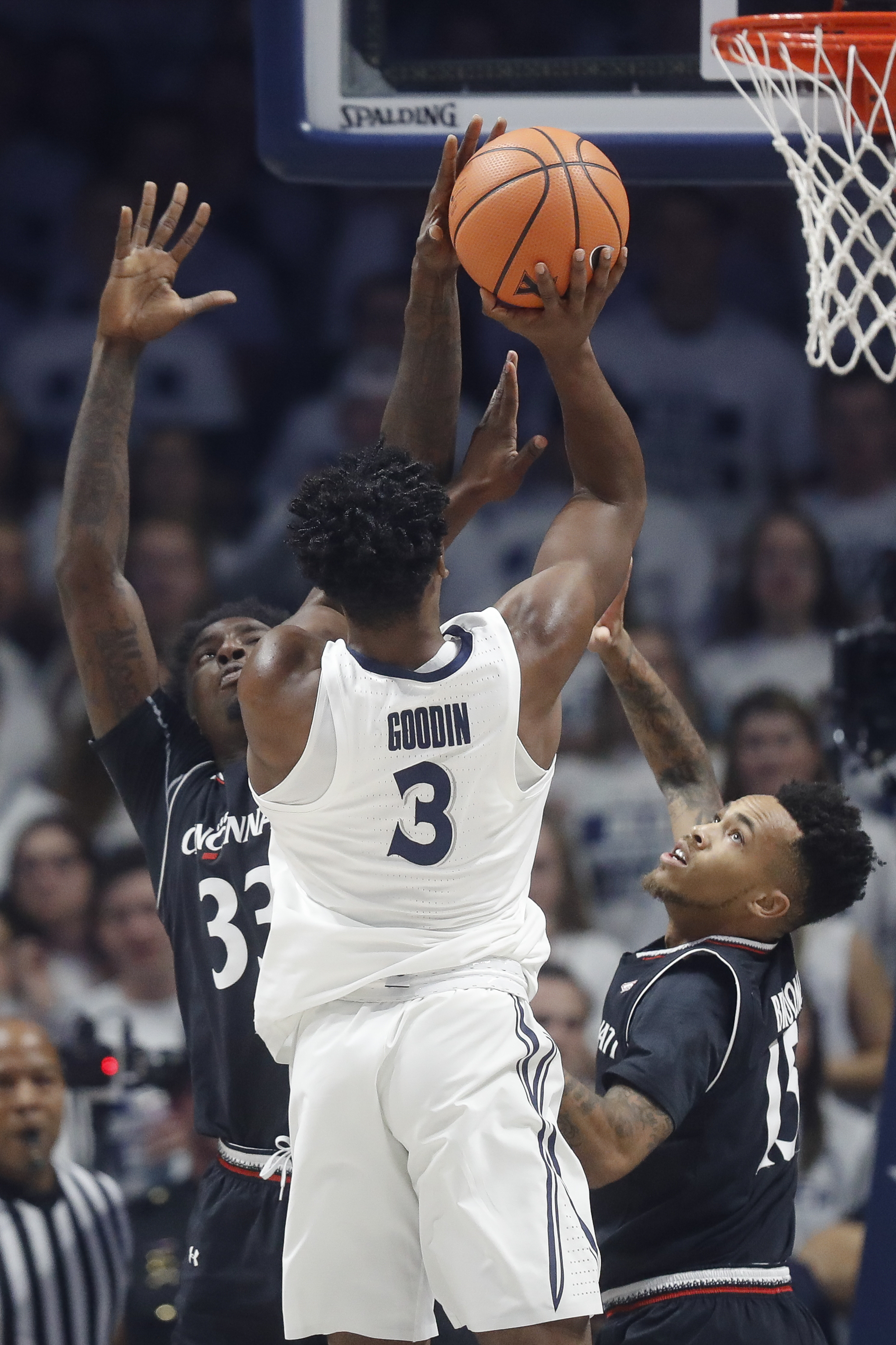 Xavier's Quentin Goodin (3) shoots against Cincinnati's Nysier Brooks (33) and Cane Broome (15) in the first half of an NCAA college basketball game, Saturday, Dec. 2, 2017, in Cincinnati. (AP Photo/John Minchillo)