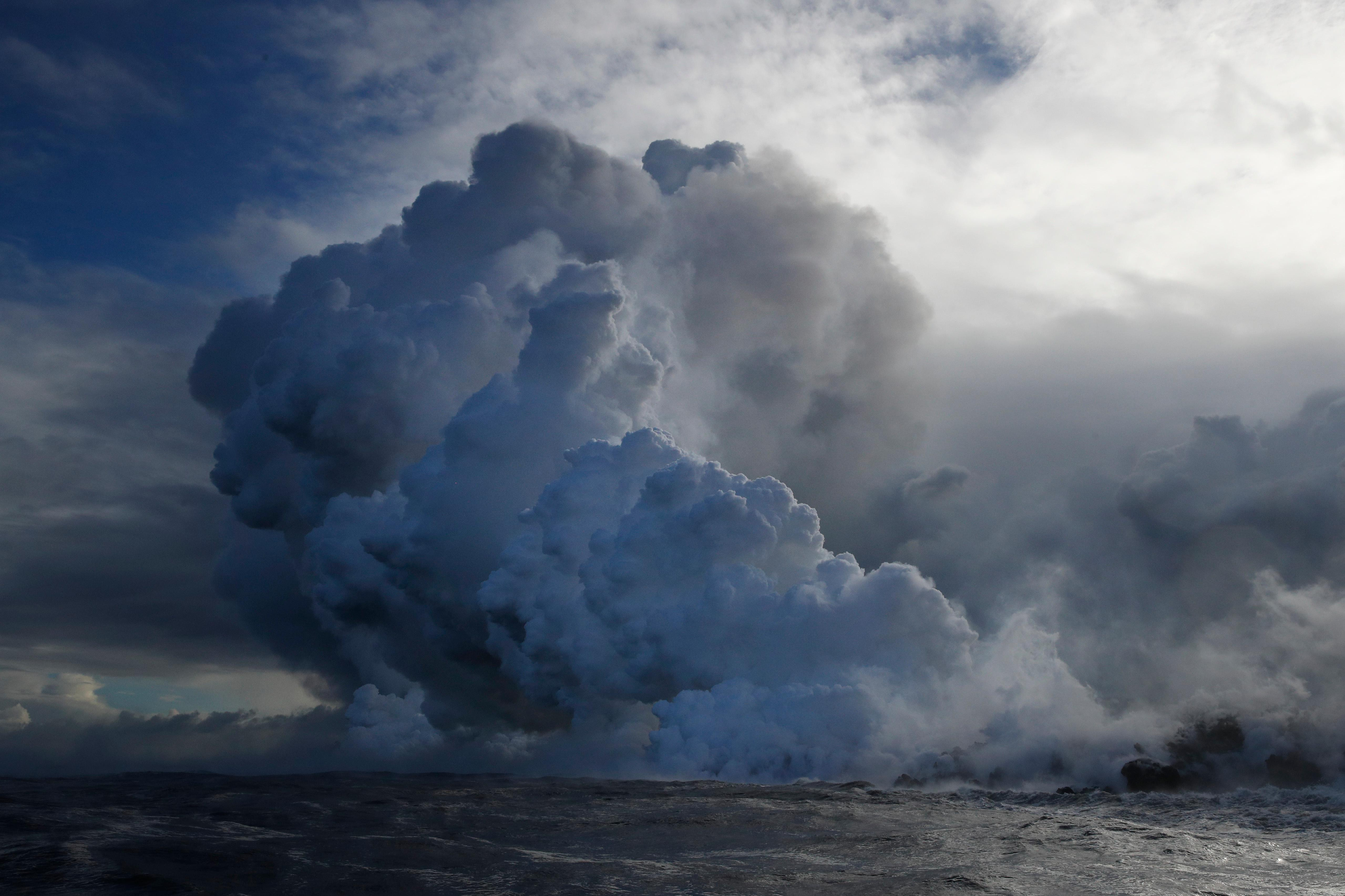 Plumes of steam rise as lava enters the ocean near Pahoa, Hawaii, Sunday, May 20, 2018. Kilauea volcano that is oozing, spewing and exploding on Hawaii's Big Island has gotten more hazardous in recent days, with rivers of molten rock pouring into the ocean Sunday and flying lava causing the first major injury. (AP Photo/Jae C. Hong)