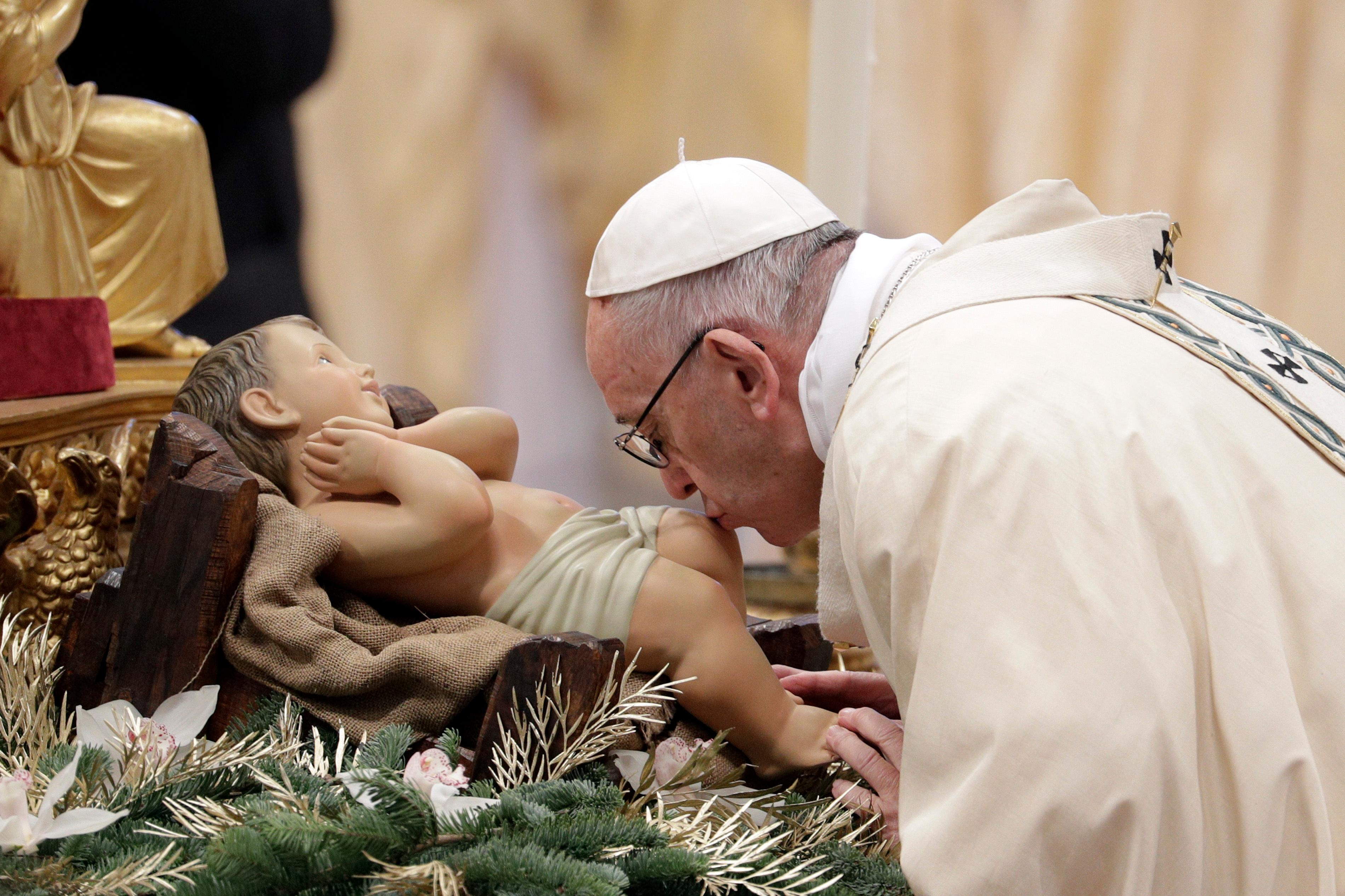 Pope Francis kisses a statue of the Divine Infant as he arrives to celebrate an Epiphany Mass in St. Peter's Basilica at the Vatican, Saturday, Jan. 6, 2018. (AP Photo/Andrew Medichini)