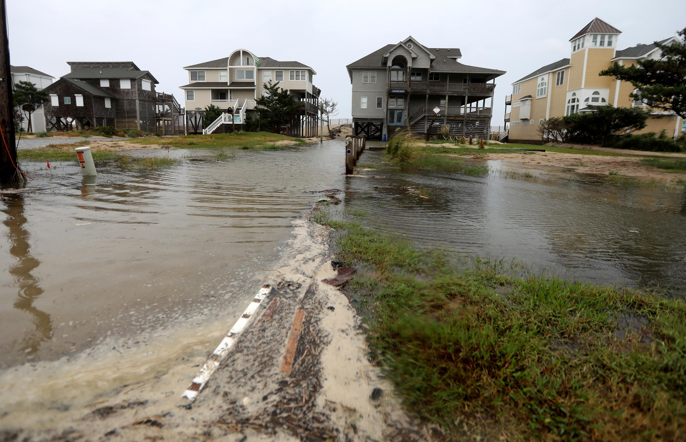 Ocean water breeches to the dunes in Avon, N.C., as the first effects of Hurricane Florence reach Hatteras Island on Thursday, Sept. 13, 2018.   (Steve Earley/The Virginian-Pilot via AP)